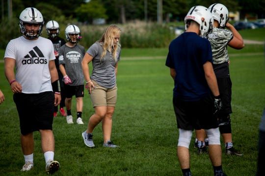 In this Thursday, Sept. 6, 2018, photo former Grand Blanc linebacker and homecoming queen Alicia Woollcott walks onto the practice field during Grand Blanc High School's football practice in Grand Blanc, Mich.