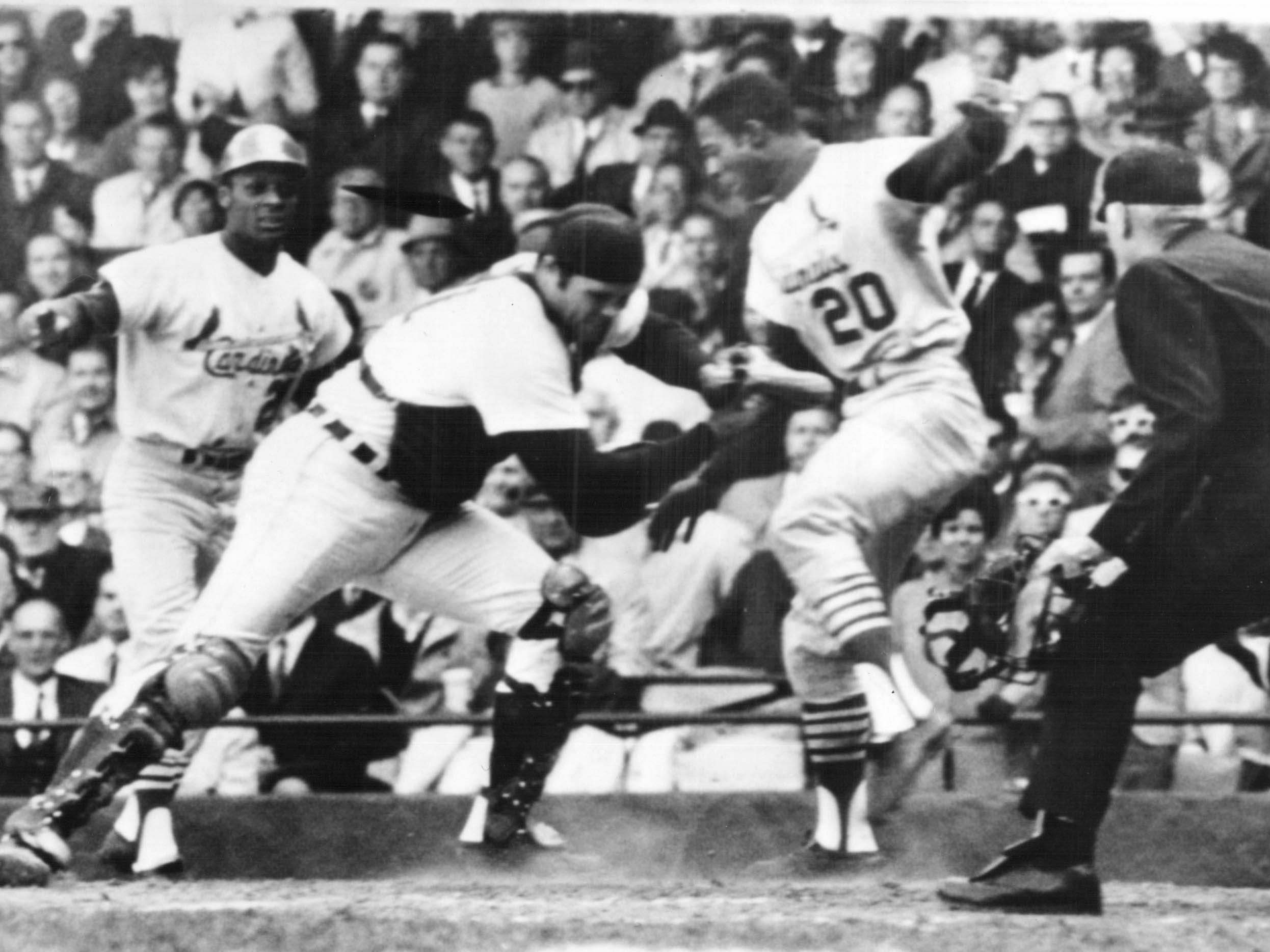 St. Louis Cardinals' Lou Brock is tagged out at home plate by Bill Freehan of the Tigers in the fifth inning of fifth game of World Series at Tiger stadium in Detroit Oct. 7, 1068. Watching is umpire Doug Harvey, right, and Curt Flood of the Cards.