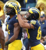 Michigan receivers Nico Collins (4) and Grant Perry (88) celebrate a Collins touchdown catch against Western Michigan during first half action Saturday, September 8, 2018, at Michigan Stadium in Ann Arbor, Mich.