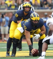 Michigan quarterback Dylan McCaffrey takes the snap from center Stephen Spanellis during the second half against Western Michigan, Saturday, Sept. 8, 2018, at Michigan Stadium.