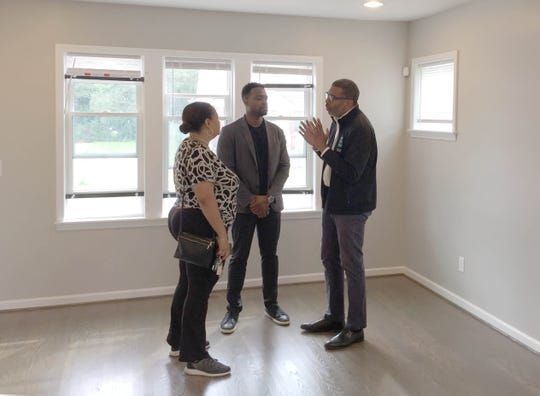 Kim Tandy, Detroit District 2 Manager, left, Century Partners co-founder David Alade, center, and Arthur Jemison, the City of Detroit's chief of services and infrastructure, had a discussion on Sept. 8, 2018 before an open house at 16557 San Juan in Detroit. They are in the first of three houses up for sale as part of the Fitzgerald revitalization project represent progress for a project that had fallen behind schedule.