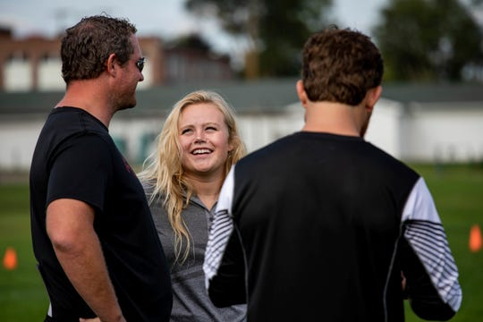 In this Thursday, Sept. 6, 2018, photo former Grand Blanc linebacker and homecoming queen Alicia Woollcott talks with coaches during Grand Blanc High School's football practice in Grand Blanc, Mich.