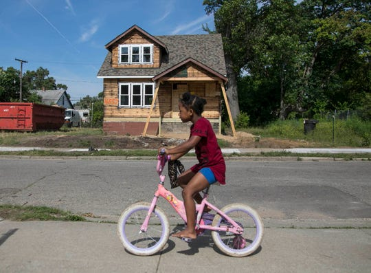 Darryona Ivory, 7, in June 2018 rides her bike past the house under renovation on 16557 San Juan in Detroit. In September, the house became available for $65,000.