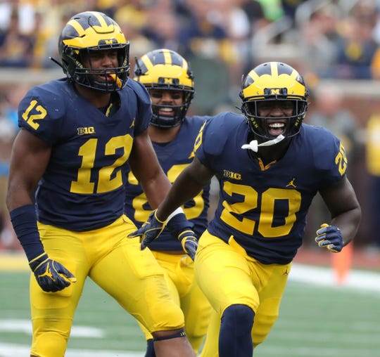 Michigan defenders Josh Ross (12) and Brad Hawkins (20) celebrate a stop during the second half against Western Michigan, Saturday, Sept. 8, 2018, at Michigan Stadium in Ann Arbor.