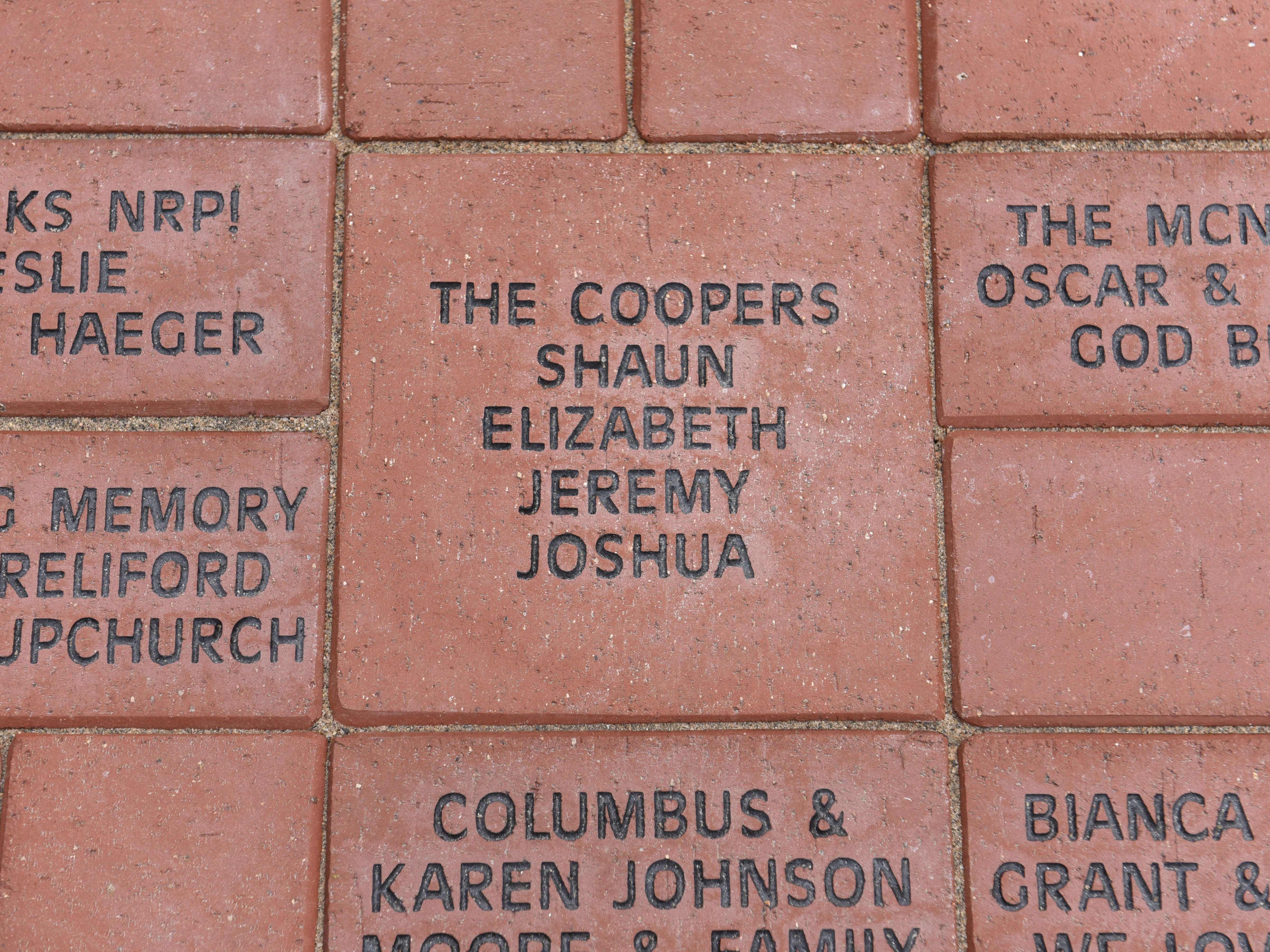 Elizabeth Cooper of Detroit shows her engraved brick paver with the names of her family during a dedication ceremony of a sculpture by artist Charles McGee at The North Rosedale Park in Detroit.