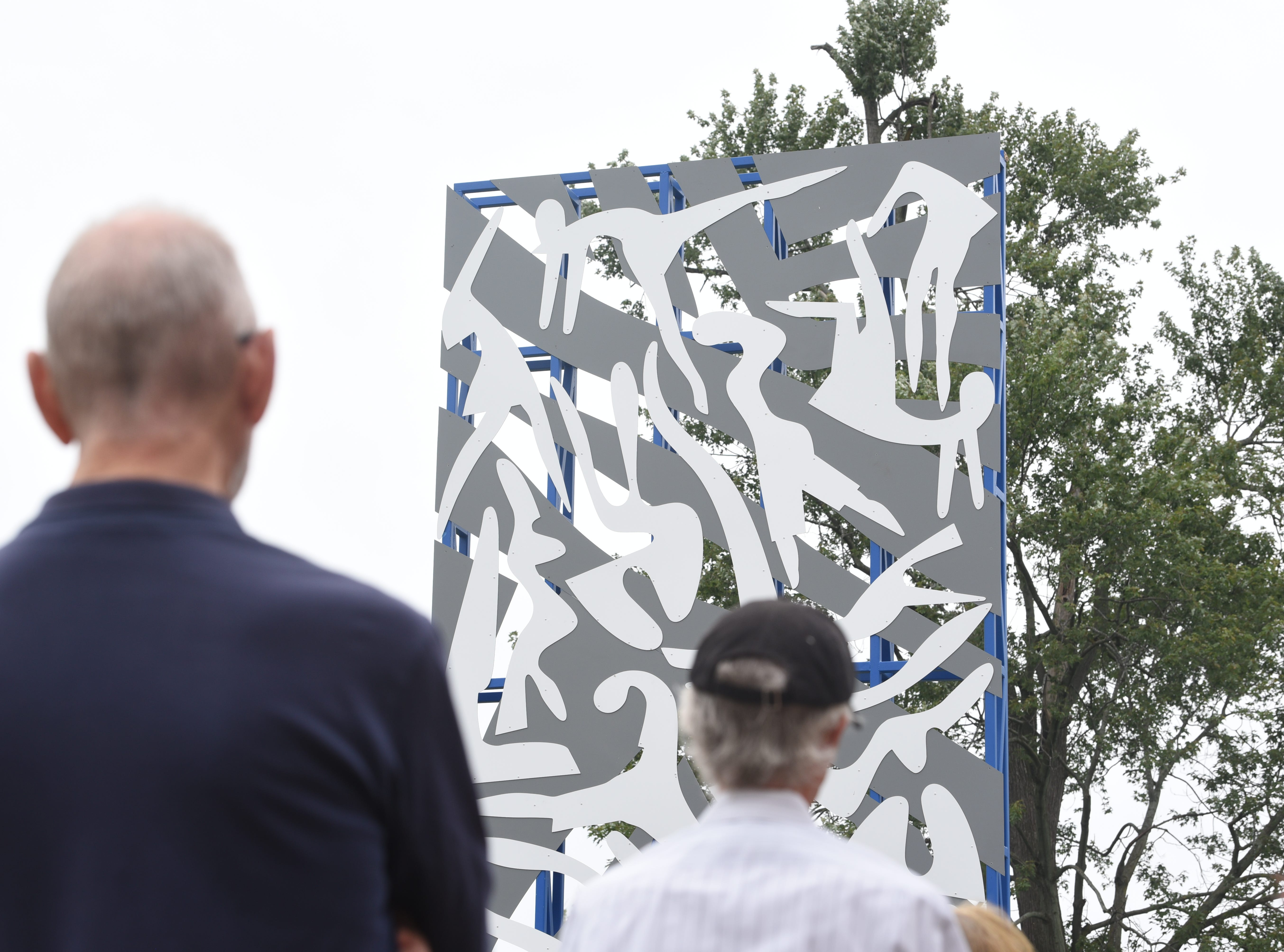 The 24-foot sculpture, entitled Unity North is comprised of steel and aluminum, with a vibrant blue steel base and vertical core faced with grey aluminum panels and 22 figures in white on each side by artist Charles McGee.