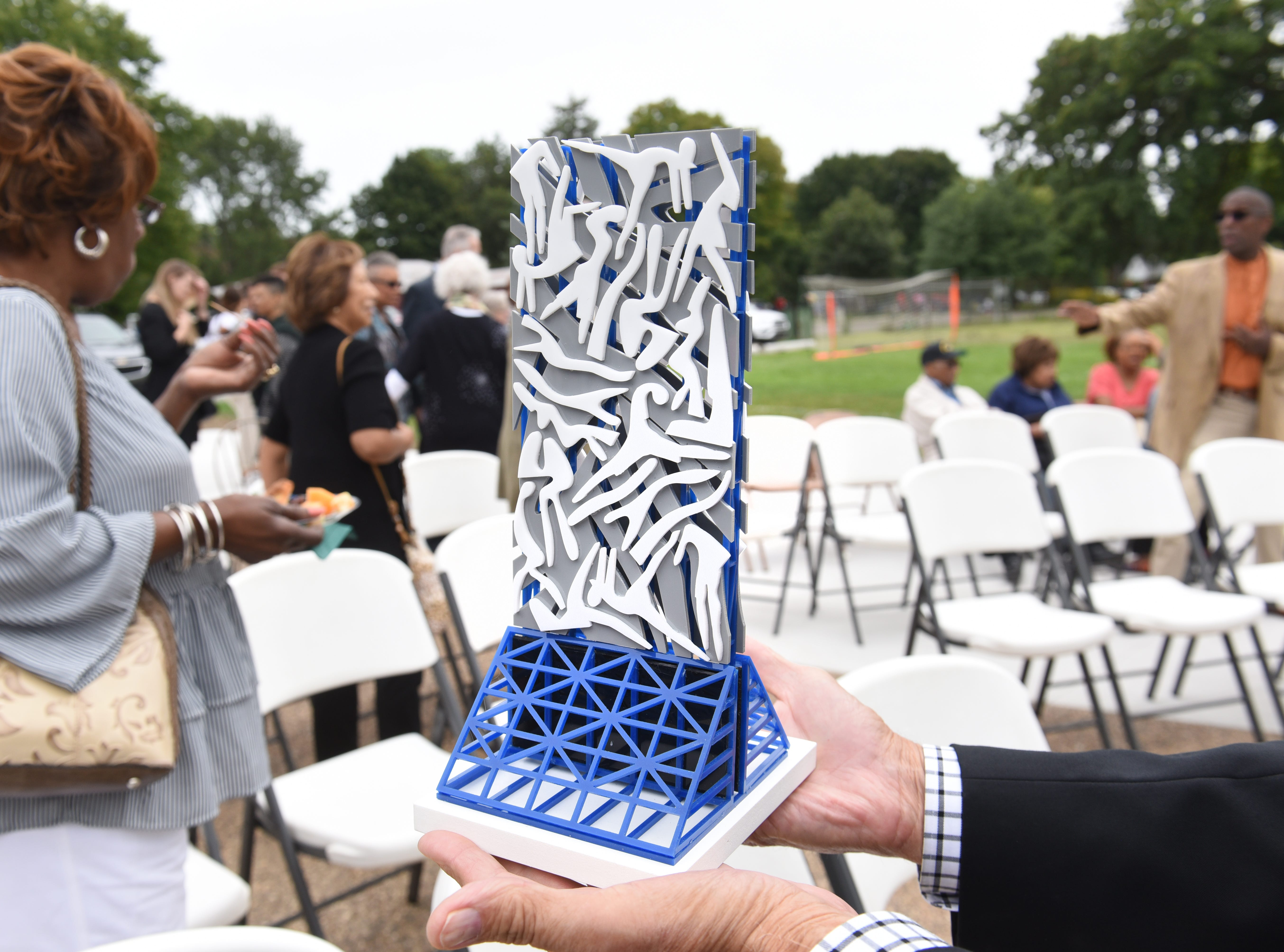 Hank Muranski holds a model of the 24-foot sculpture sculpture by artist Charles McGee.