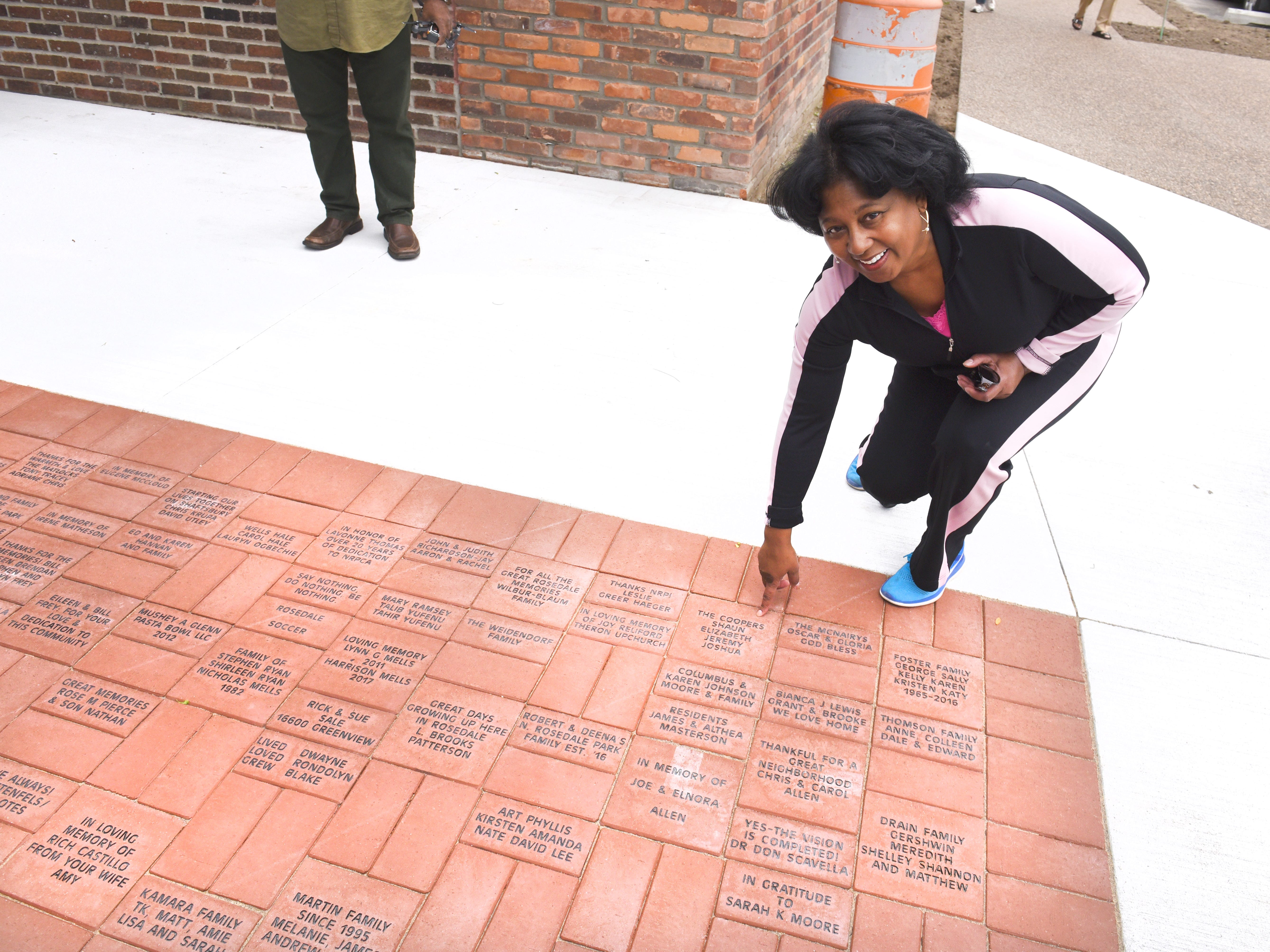 Elizabeth Cooper of Detroit points to her engraved brick paver installed outside the Community House during a dedication ceremony.
