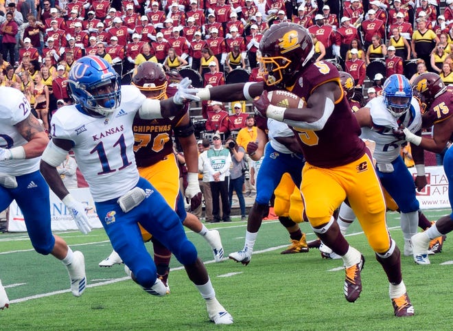 Central Michigan running back Jonathan Ward (5) carries the ball as Kansas safety Mile Lee (11) closes in on Saturday.