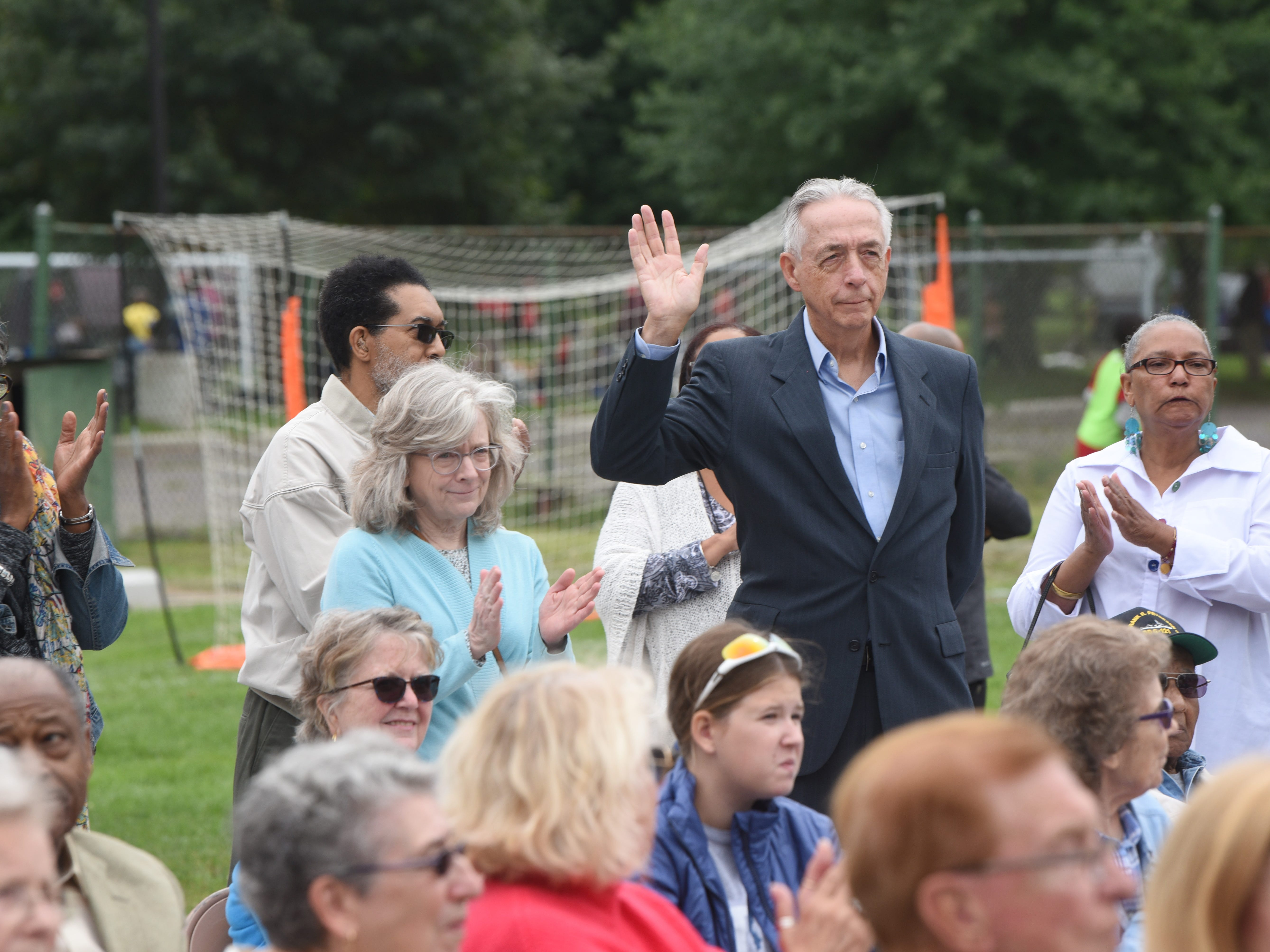 Bill Frey, right, president, North Rosedale Park Community Association,  waves to the crowd during the dedication ceremony.