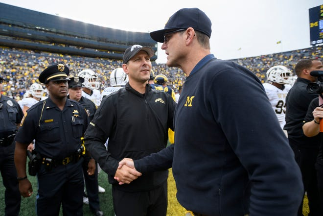Western Michigan head coach Tim Lester, left, and Michigan head coach Jim Harbaugh shake hands after the game earlier this year.