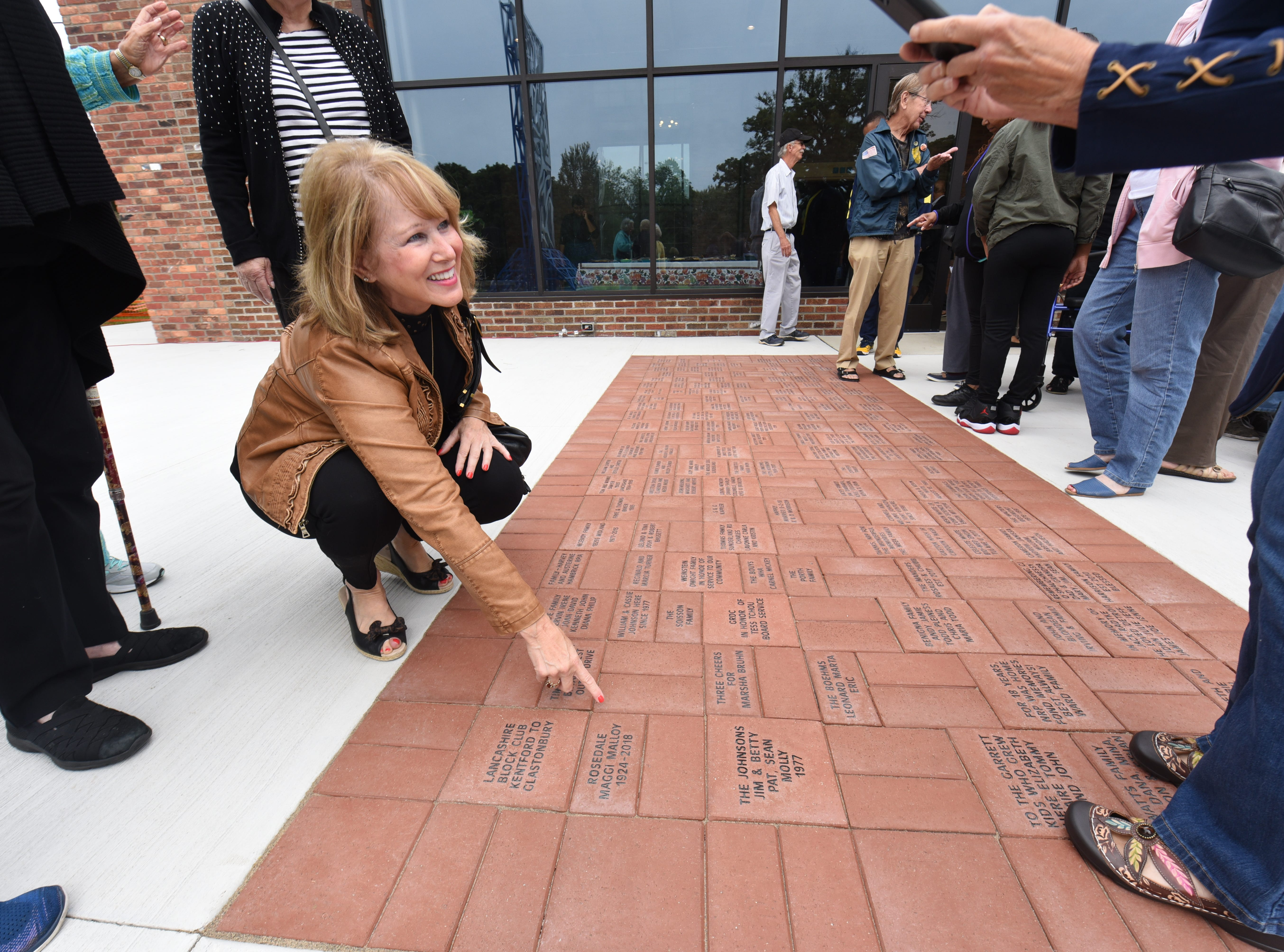 Carole Layne of Livonia points to a memorial engraved brick paver installed outside the Community House at North Rosedale Park in Detroit.
