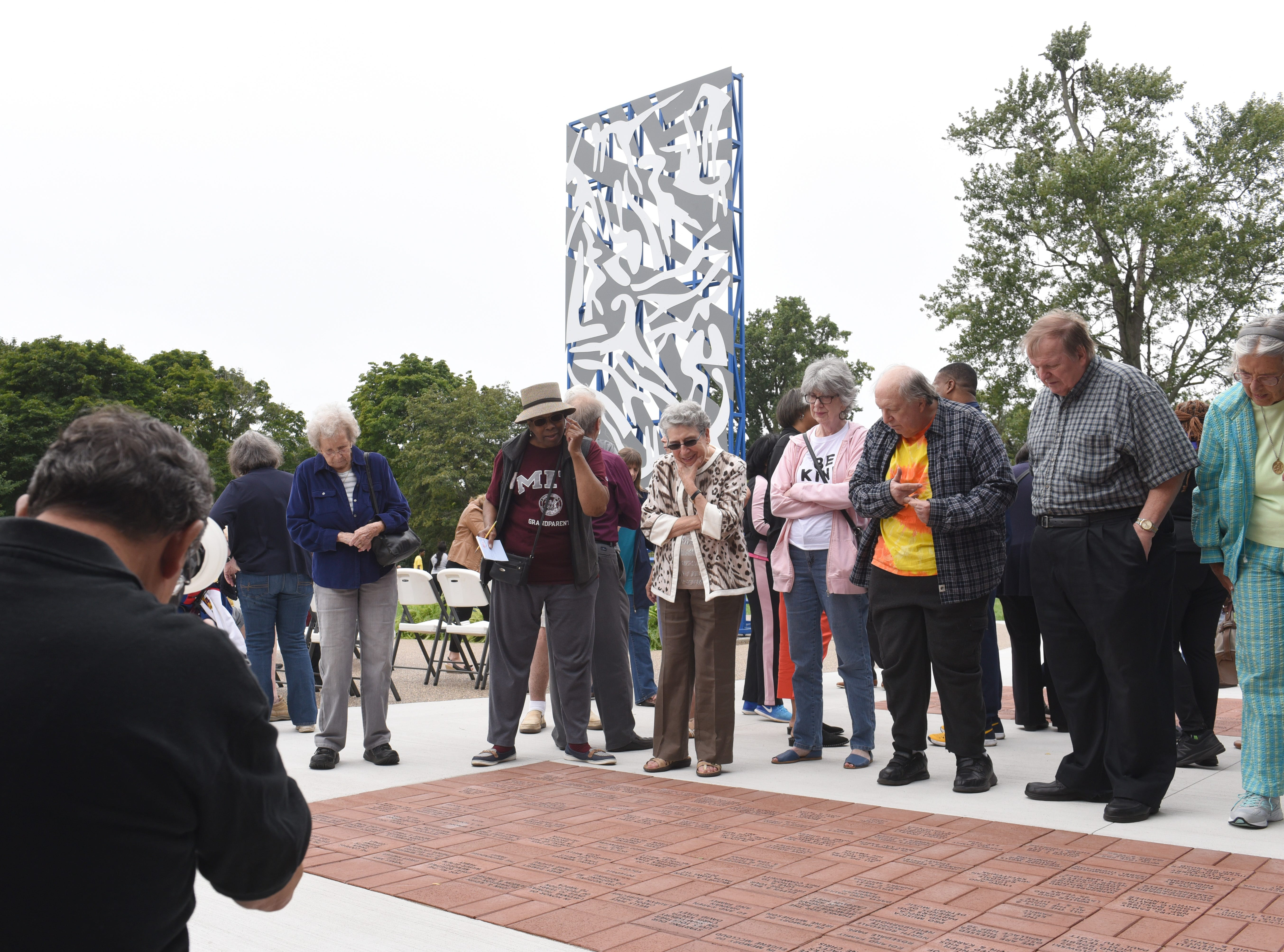 People gather outside the Community House during a dedication ceremony of a sculpture by artist Charles McGee at  North Rosedale Park.