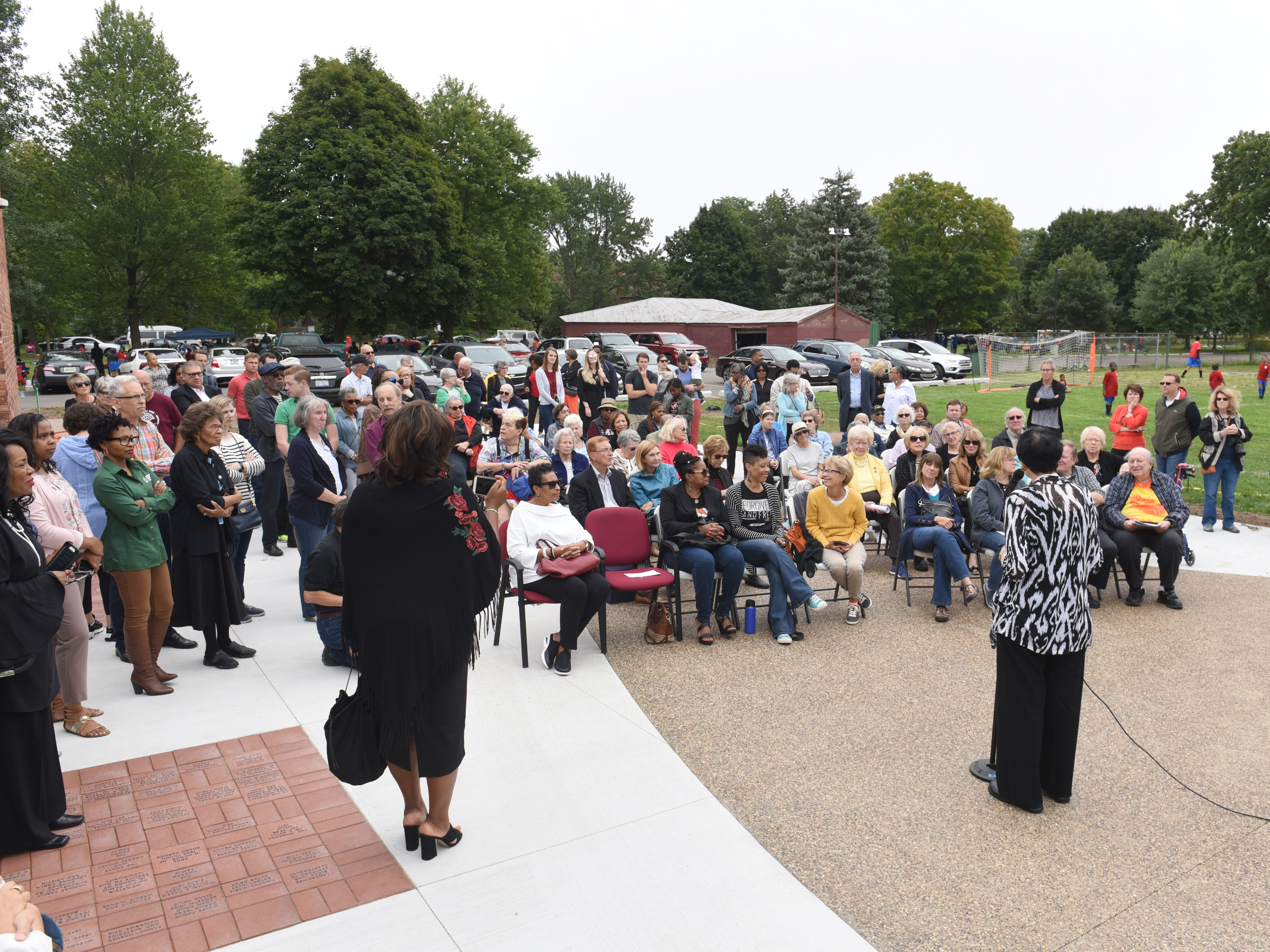 Marsha S.  Bruhn, chair, The Legacy Project of North Rosedale Park,  speaks during a dedication ceremony of a sculpture by artist Charles McGee at The North Rosedale Park Community House in Detroit on Saturday.