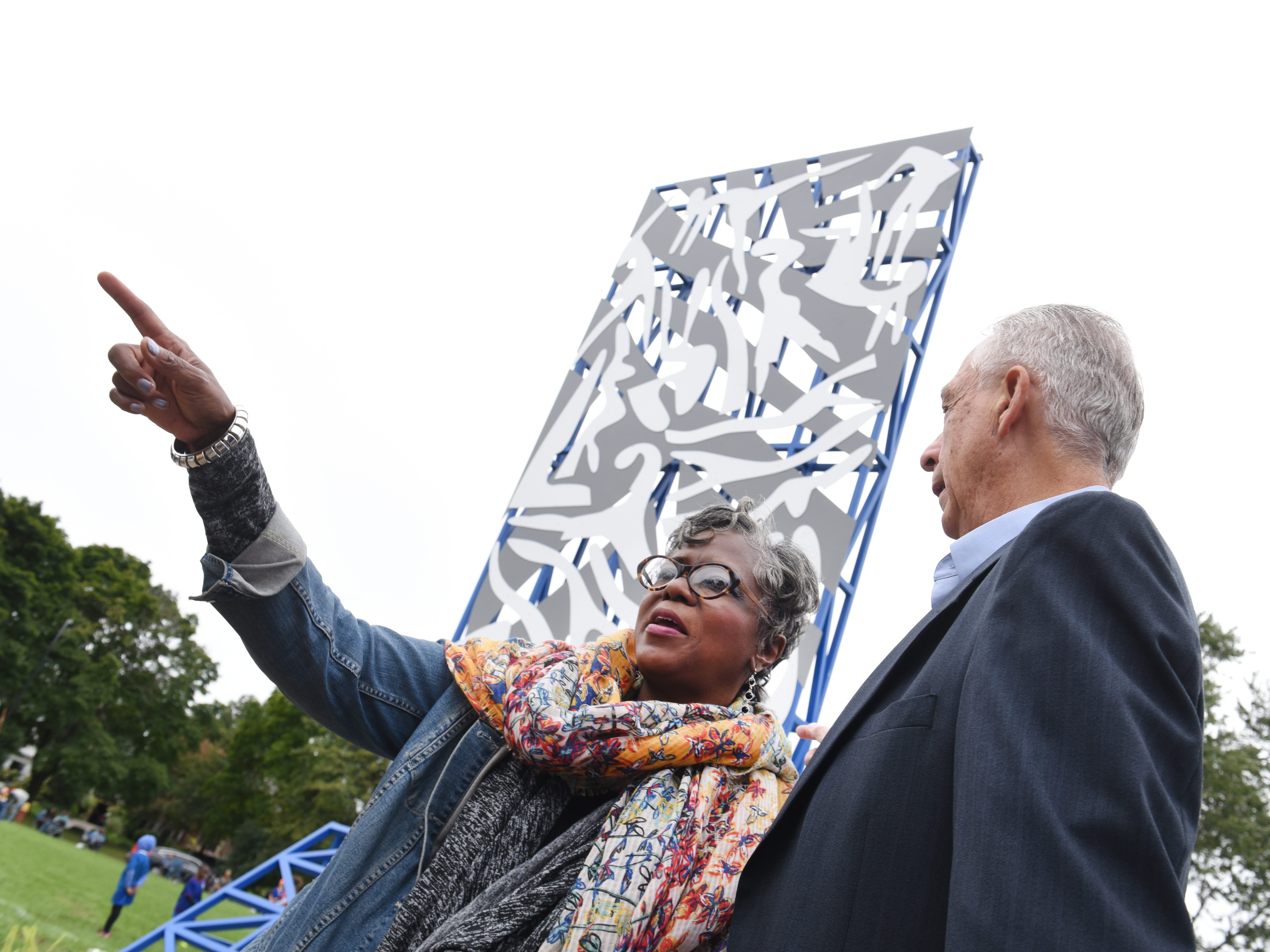 Domeda McCauley, former co-chair for the Great Art Great Park, with Bill Frey, president, North Rosedale Park Community Association, at the newly installed sculpture by renowned artist Charles McGee at The North Rosedale Park Community House.