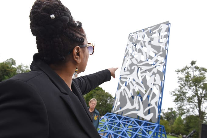 """April McGee-Flournoy, daughter of Charles McGee, points to the newly installed sculpture by her father artist Charles McGee at The North Rosedale Park Community House in Detroit on Saturday, September 8, 2018. The 24-foot sculpture, titled """"Unity North,"""" is comprised of steel and aluminum, with a vibrant blue steel base and vertical core faced with grey aluminum panels and 22 figures in white on each side."""