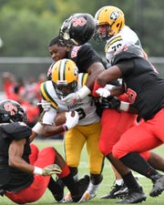 The helmet of Oak Park's Justin Rogers pops off while he tries to make a tackle last season.
