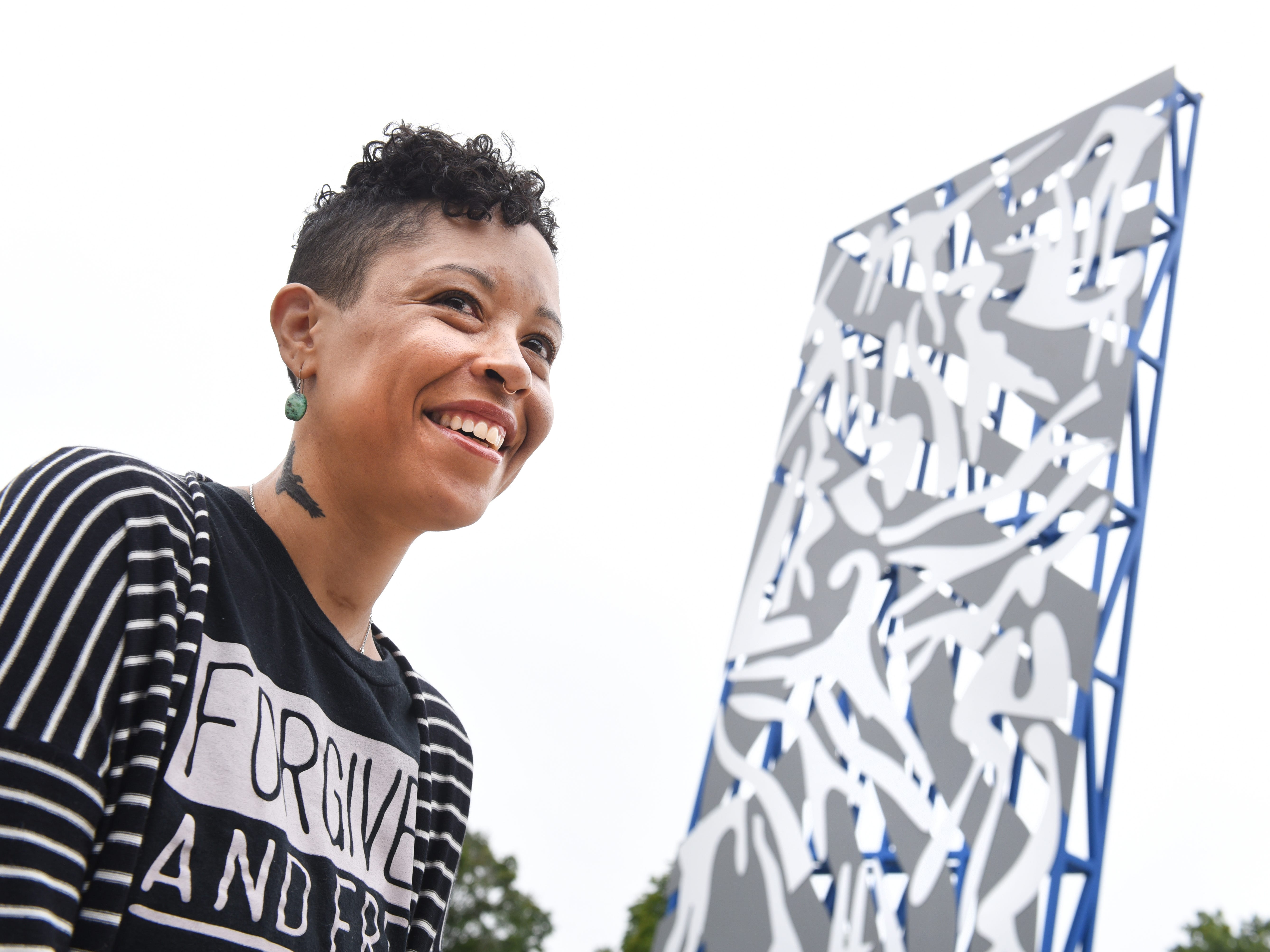 """Lyndsay McGee, daughter of Charles McGee, stands next to the newly installed sculpture by her father renowned artist Charles McGee at The North Rosedale Park Community House in Detroit. The 24-foot sculpture, entitled """"Unity North,"""" is comprised of steel and aluminum."""