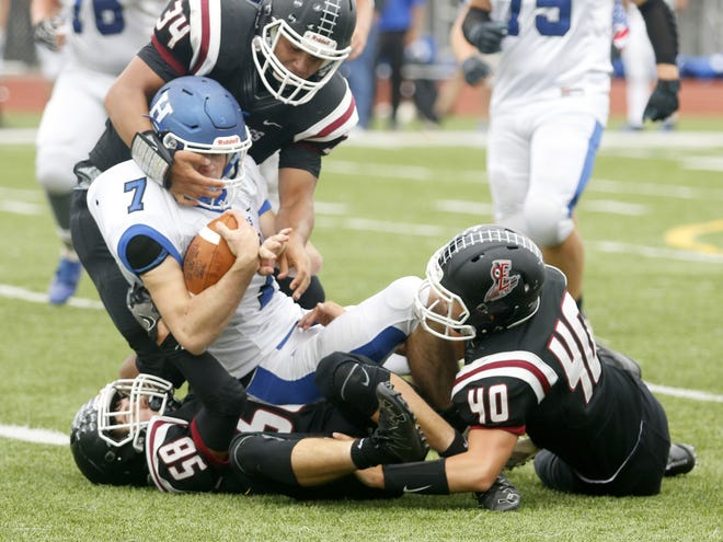 Elmira defenders Devin Hoskins (34), Thompson Miller (58) and Lucas Allen (40) bring down Gavin Elston of Horseheads on Sept. 8, 2018 during the Express' 40-27 win at Marty Harrigan Athletic Field.