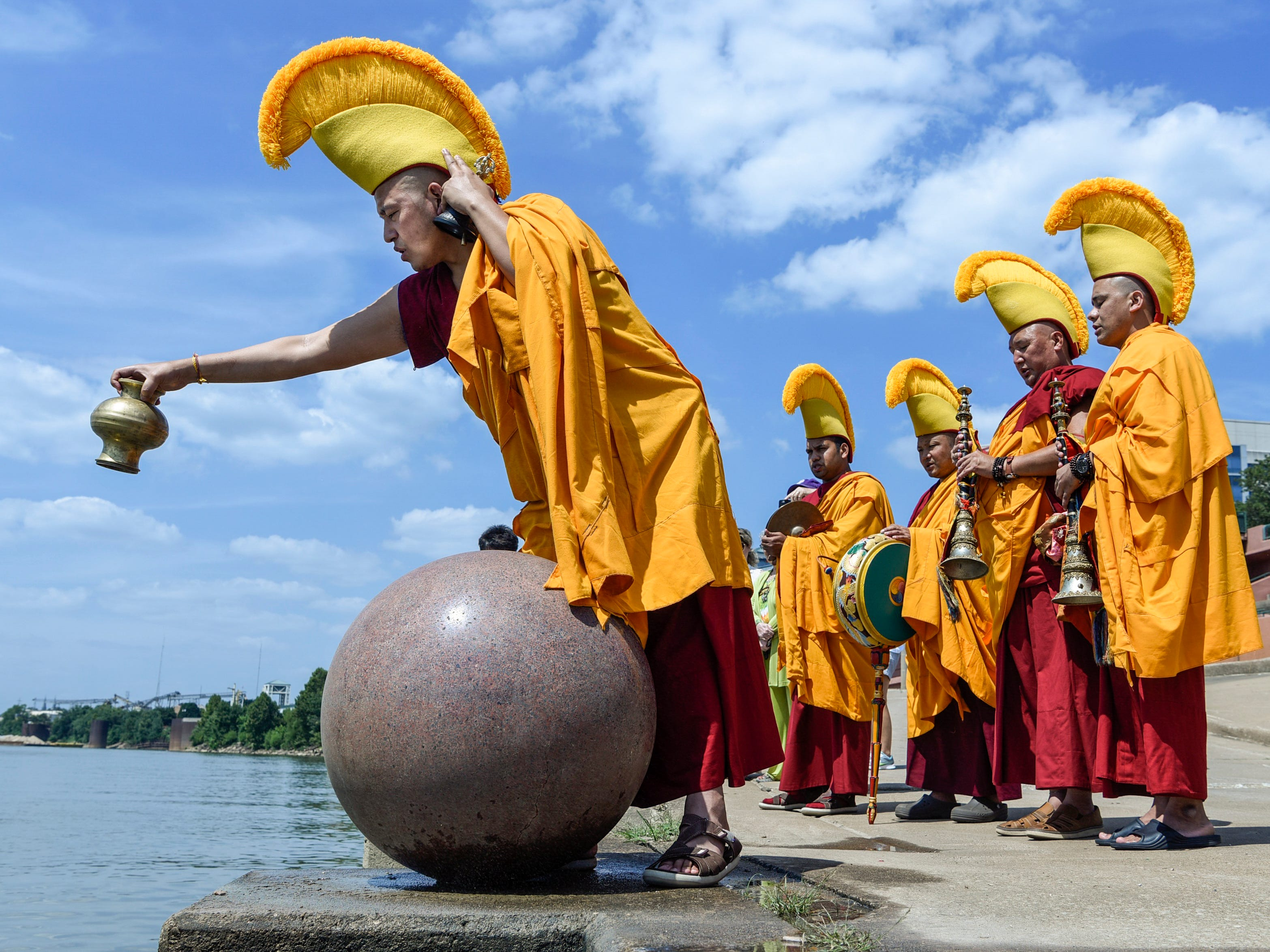 After five days of meticulous work creating a World Peace sand mandala, Tibetan monk Yeshi Rabgyal, left, disperses the colorful sand that was ceremoniously deconstructed into the Ohio River at Dress Plaza in Downtown Evansville, Thursday afternoon. The six monks visiting from Tashi Kyil Monastery in Dehra Dun, India, poured the sand into the river to spread prayers for peace and long life to Evansville residents and the world.