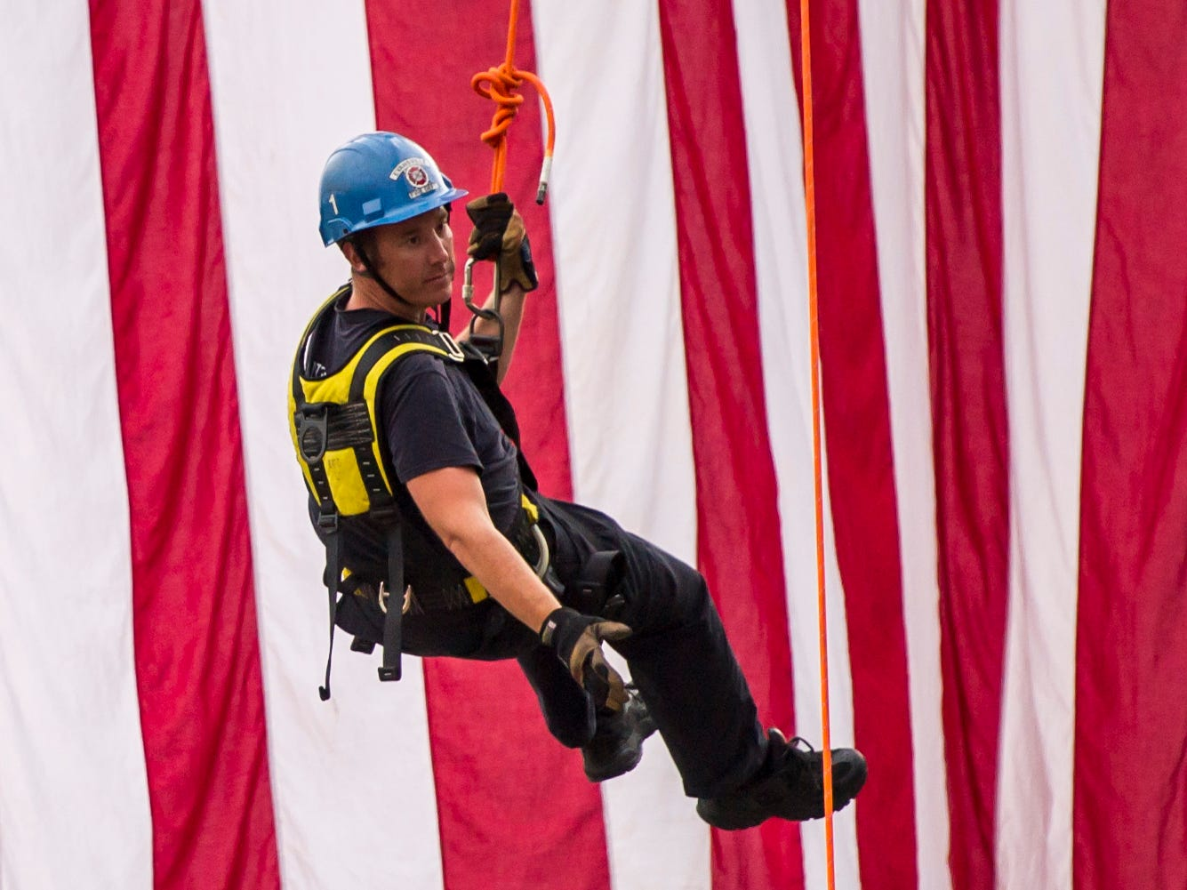 Nick Raber, member of the EFD Rope and Confined Space team, hangs from a ladder truck while the American flag waves behind him during the 35th National Night Out at Wesselman Woods Tuesday, August 7, 2018.