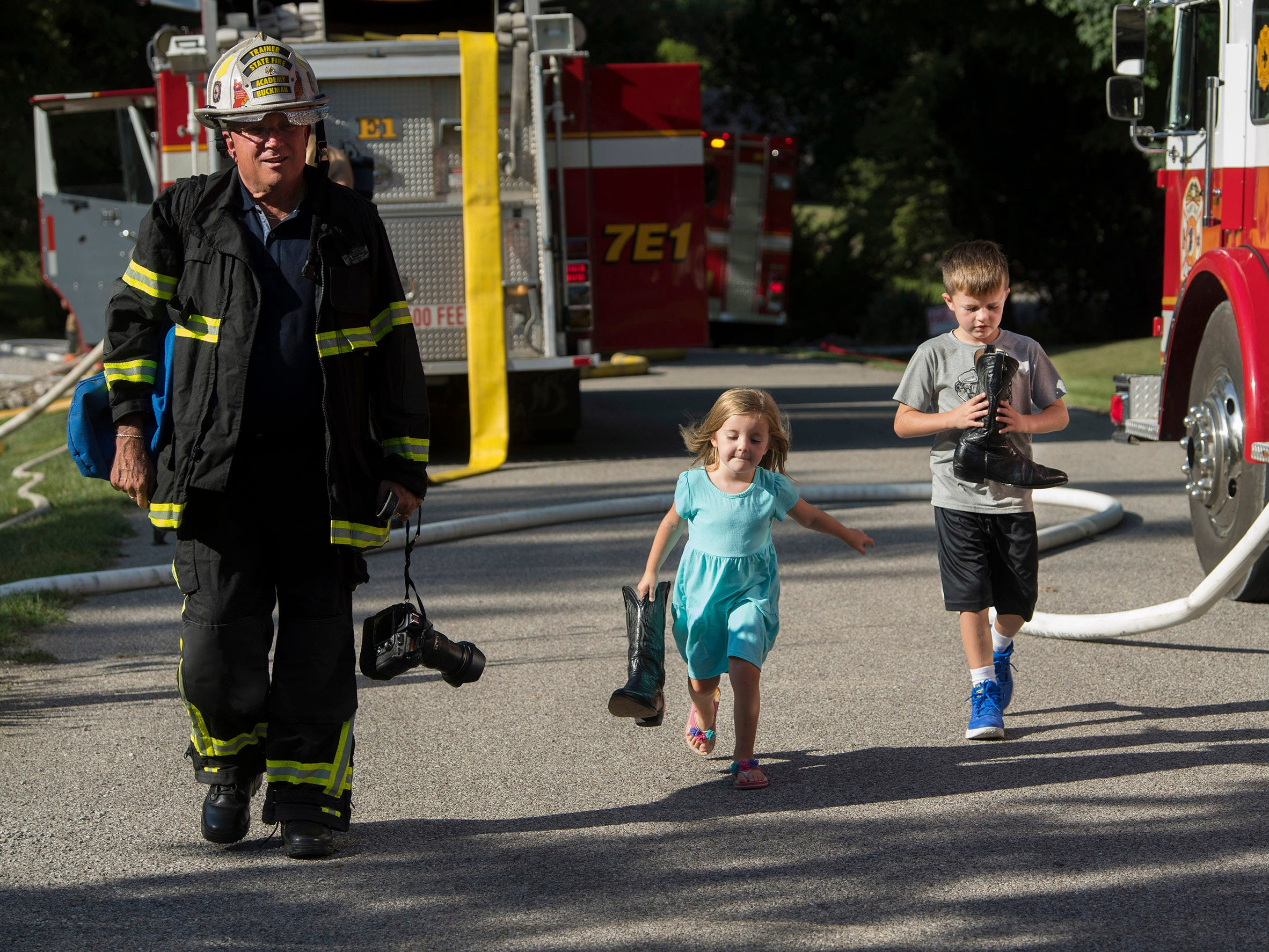 "John Buckman, left, a chief retired after 35 years with the German Township Fire Department, heads back to his vehicle with his grandkids, Kate, 5, and Nicholas Wood, 8, hauling his cowboy boots from a fire at 630 Marlene Drive in Evansville Tuesday evening. ""We were at the bank when I heard the second alarm fire,"" Buckman said of their delayed date at McDonald's for ice cream. ""I said, 'Kids, we're going to go see the fire first. See if we can help.' It's the life of a volunteer firefighter,"" he continued. ""You drop what you're doing and go help people."" (Shot 8/28/18)"