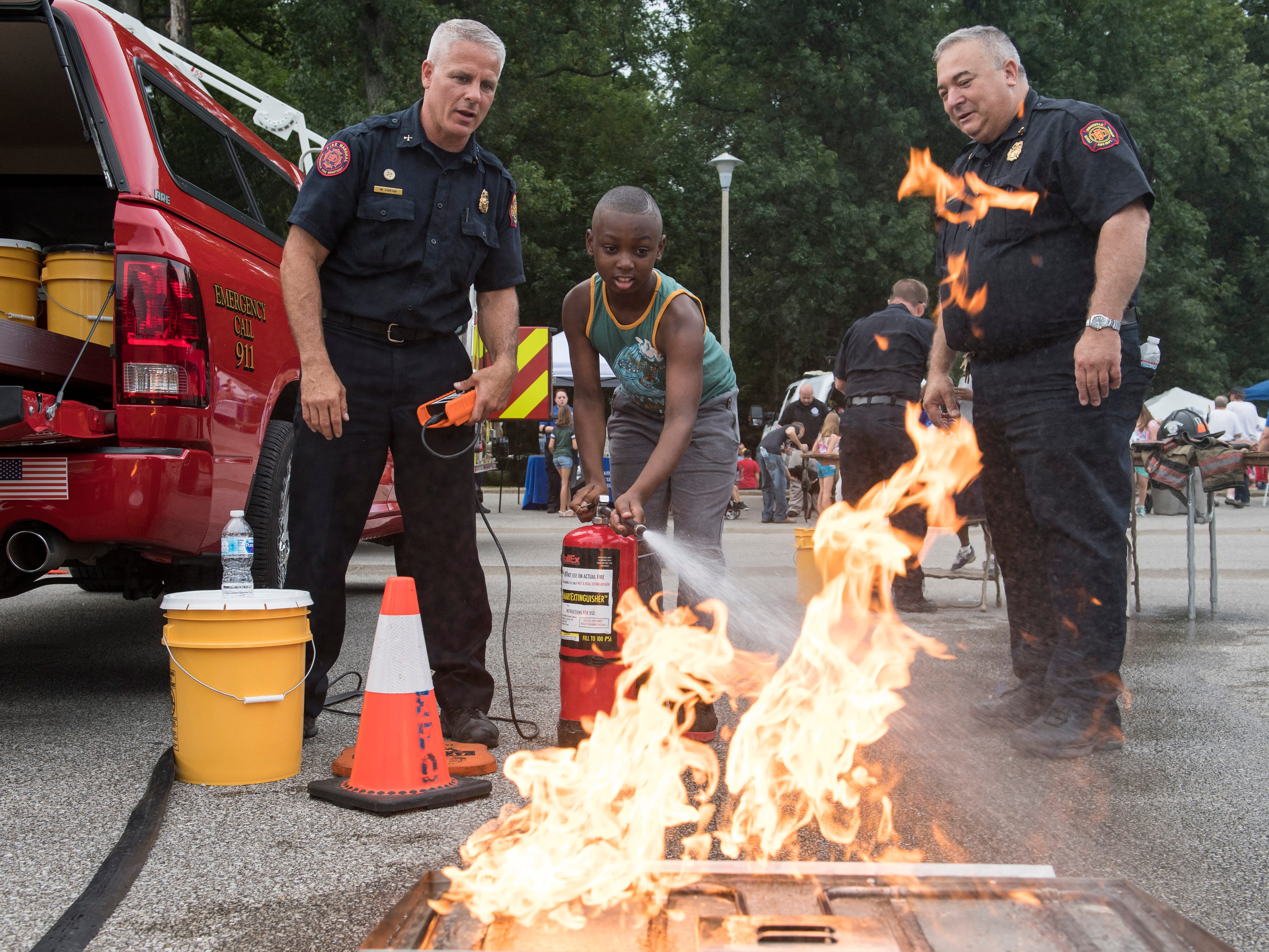 Andre Jones, center, receives guidance from Evansville Firefighters Mike Doran, left, and Joe Mayer, right, on how to properly extinguish a fire during the 35th National Night Out at Wesselman Park, Tuesday, August 7, 2018.