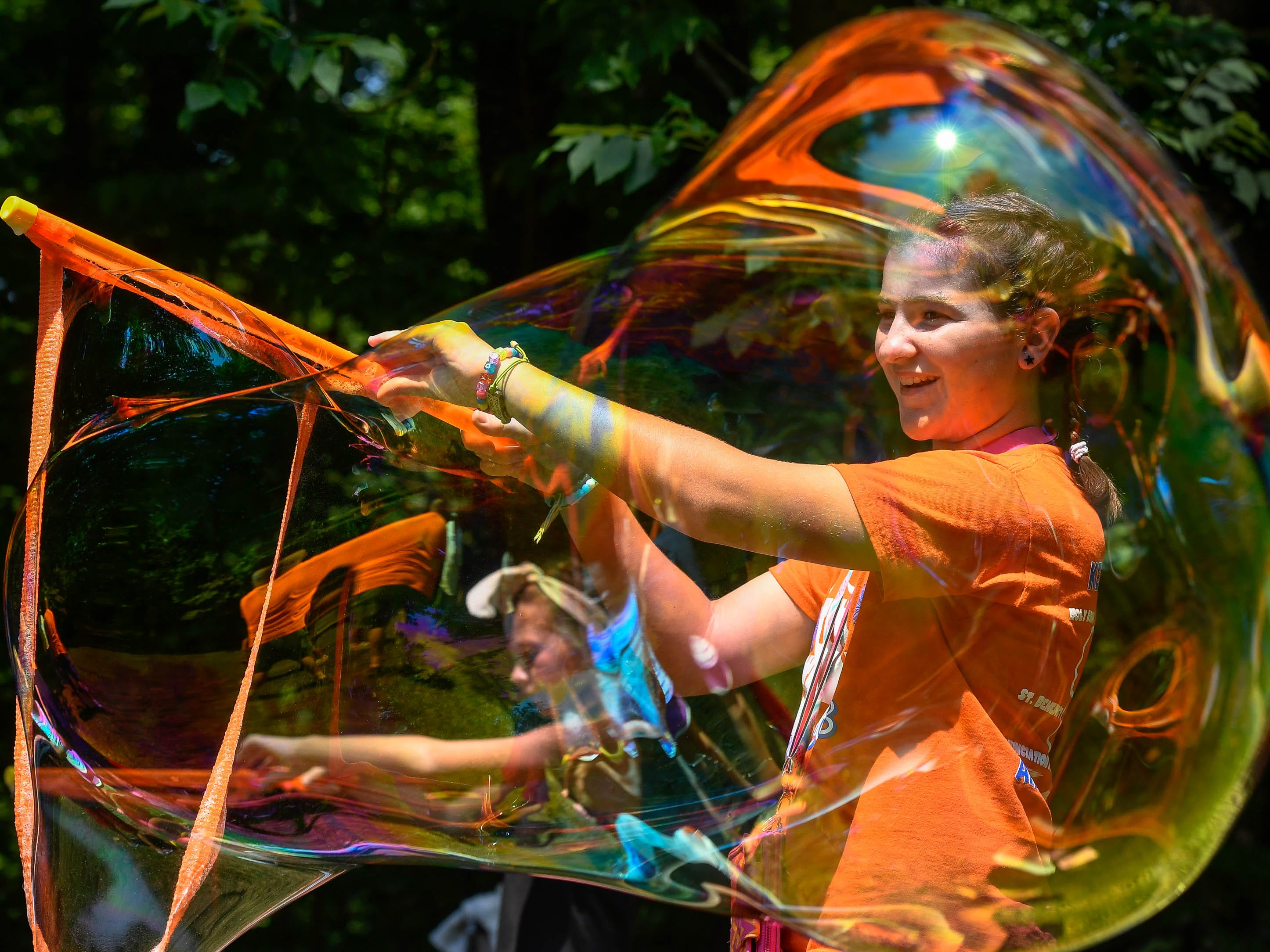 Lydia Jones, 12 years-old, makes a giant soap bubble during the back to school Party in the Park event held at John James Audubon State Park Saturday, August 4, 2018.