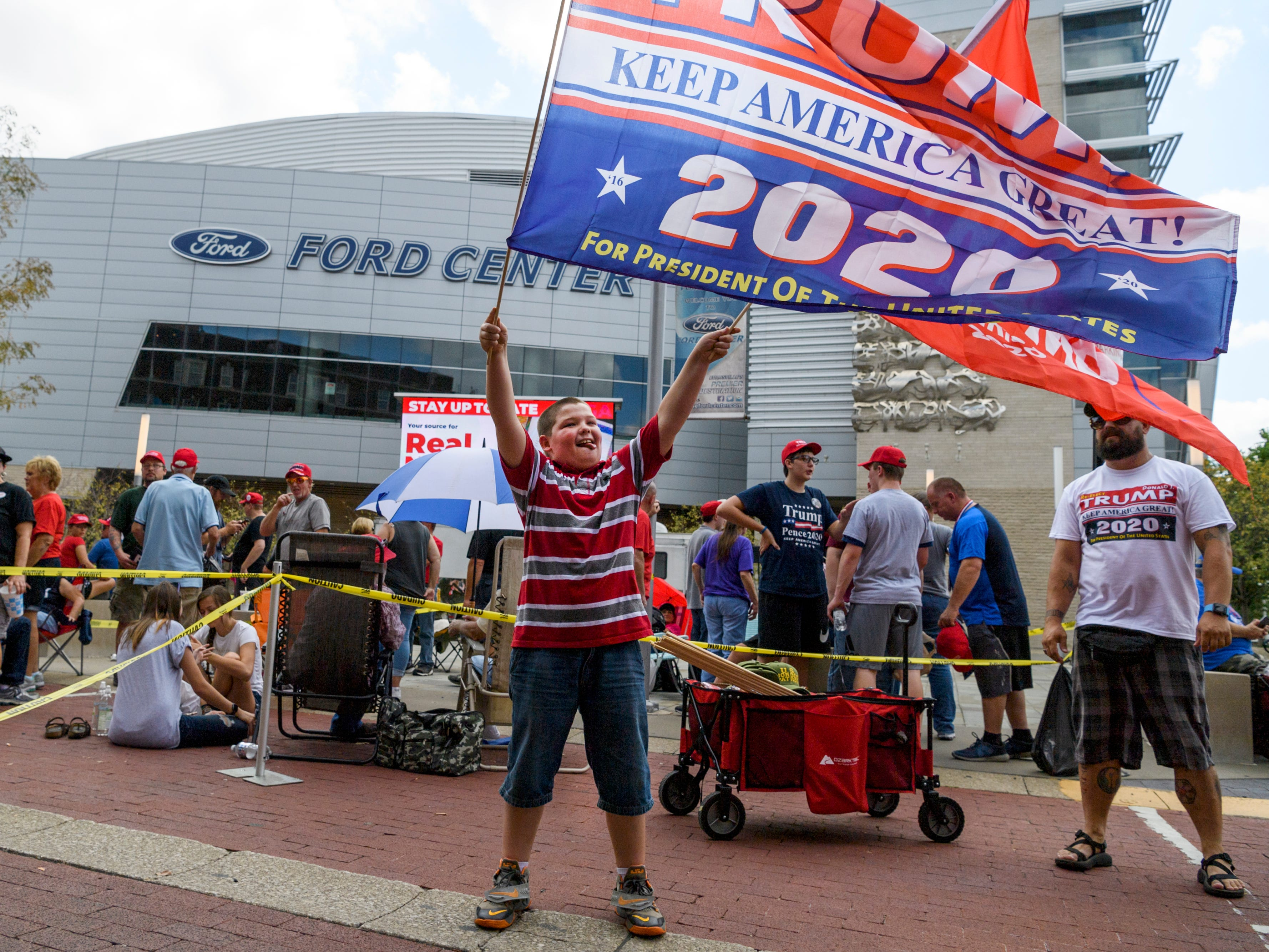 "Landon Pfingston, 10, waves flags among the crowd of people lining up outside the Ford Center in Downtown Evansville for President Donald Trump's Make America Great Again rally, which is scheduled to start at 7 p.m. Thursday, Aug. 30. ""It's history in the making,"" Pfingston's father Eduardo Gonzales III said about bringing him to the rally. ""He wanted to come and this is the first time he gets to see a President in real life."""