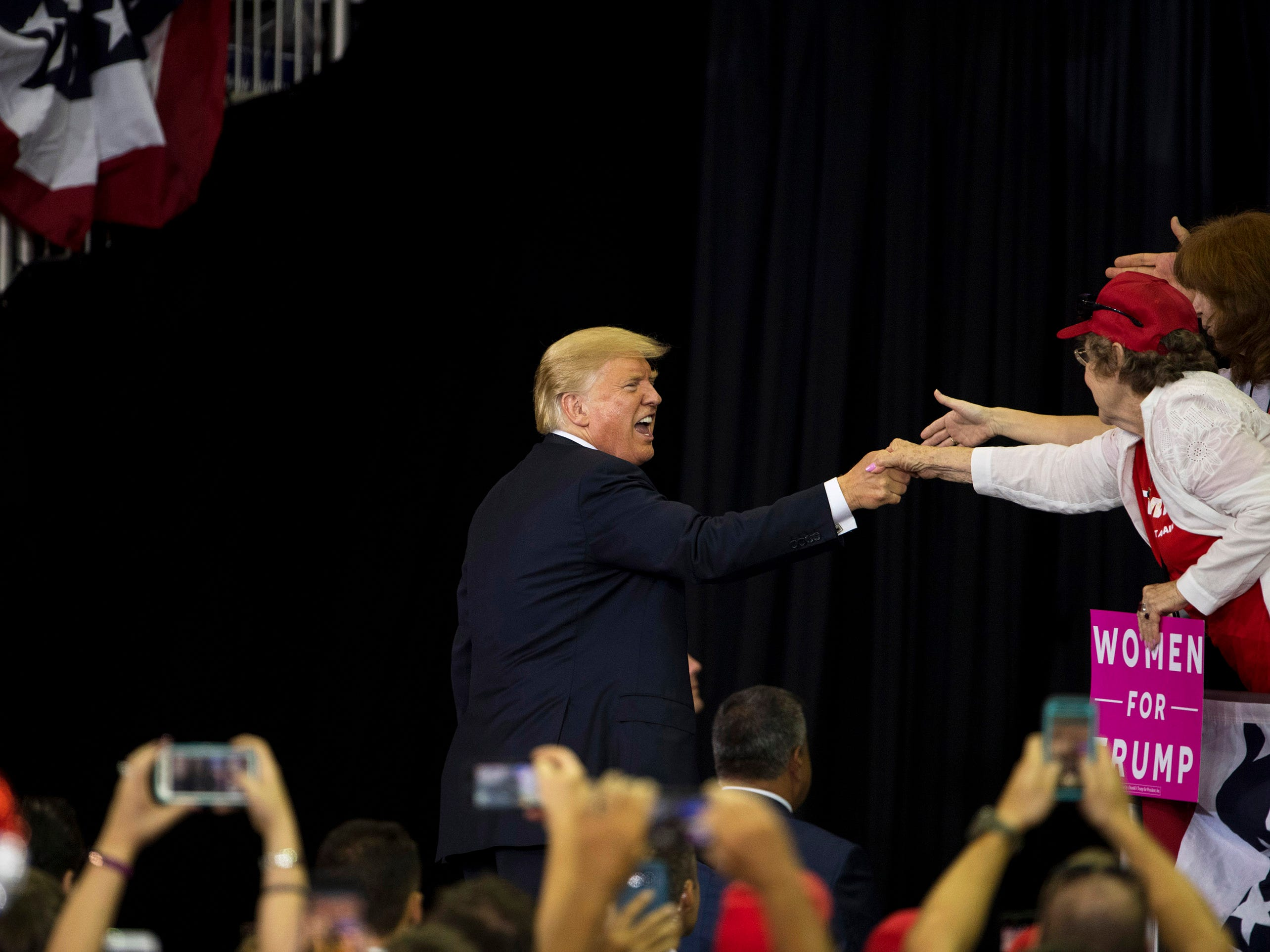 President Donald Trump shakes hands as he exits the stage after his campaign rally at the Ford Center in Evansville, Ind., Thursday night, August 30, 2018.