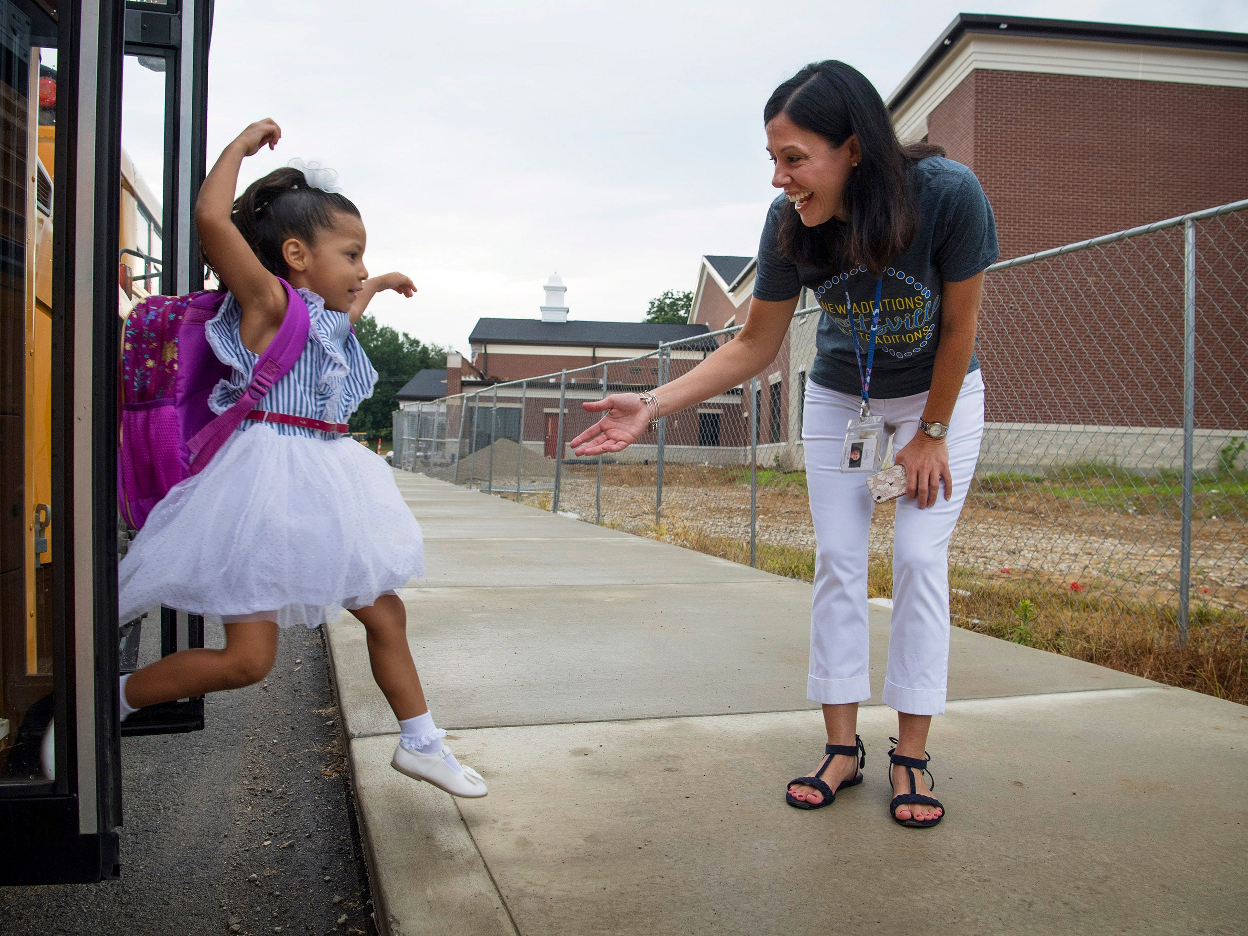 Kindergartener Galilea Guivas, 5, leaps from the school bus to embrace Principal Sarah Estabrook on her first day of school at Spottsville Elementary School, Wednesday morning, August 8, 2018.
