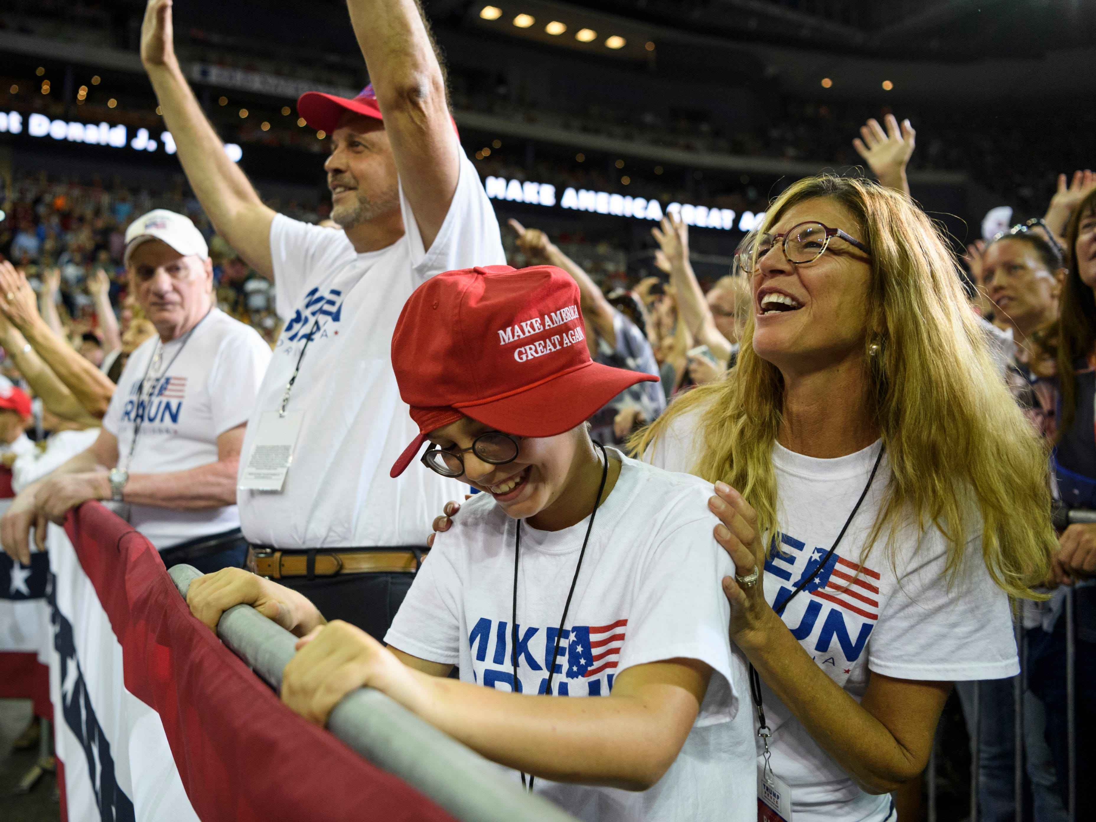 Jasper residents Samuel Osterman, 11, front center, Melissa Osterman, right, and Merrill Osterman, back, cheer with the crowd as they stand in front of the podium for President Donald Trump's Make America Great Again rally in support of U.S. Senate candidate Mike Braun at the Ford Center in Evansville, Ind., Thursday, Aug. 30, 2018.