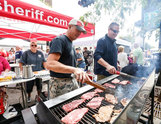 Chris Dobyns and Jon Anthes cook steaks at the Fond du Lac Sheriff's booth Saturday, Sept. 8, 2018, at Fondue Fest in downtown Fond du Lac, Wis.