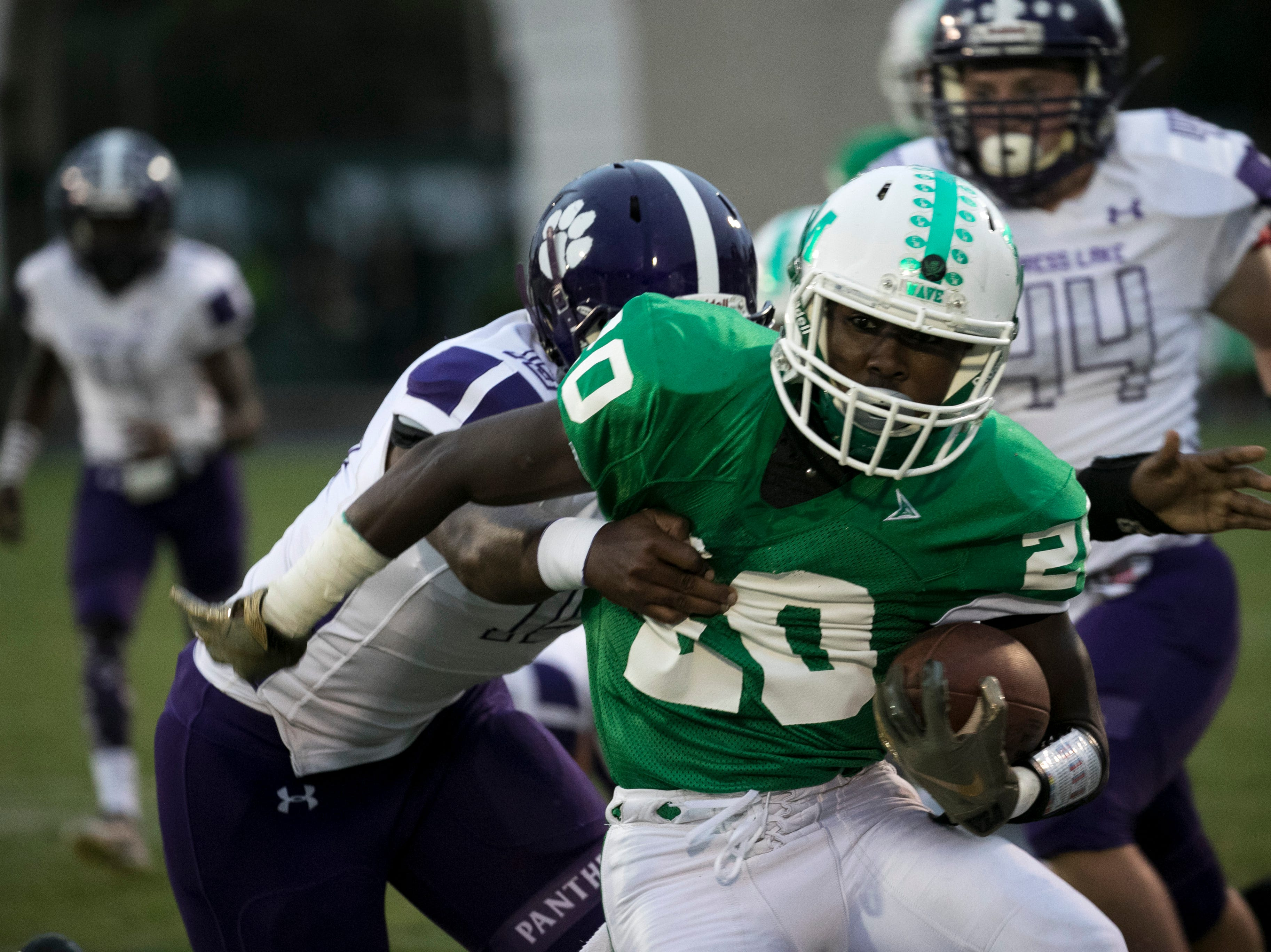 Milan Tucker of Fort Myers is tackled by Cypress Lake's Darren Tobias on Friday night, September 7, 2018, at Fort Myers High School.