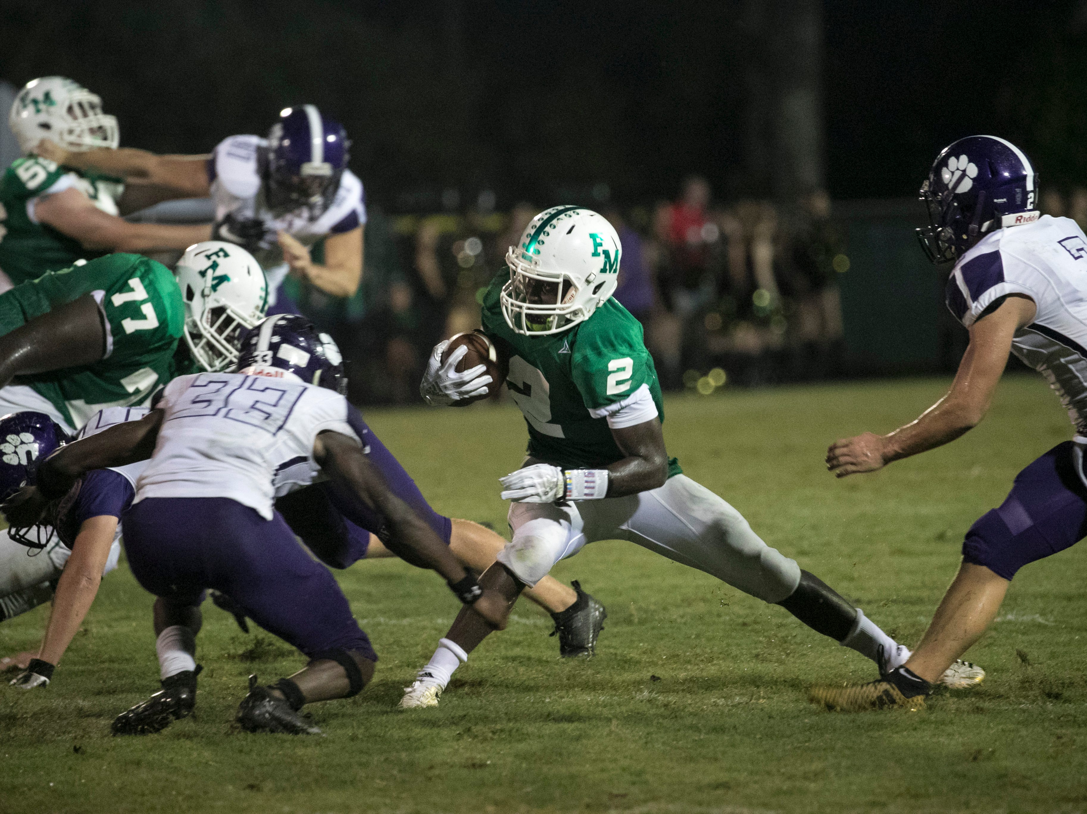 Fort Myers running back Sias Young runs the ball against Cypress Lake on Friday night, September 7, 2018, at Fort Myers High School.