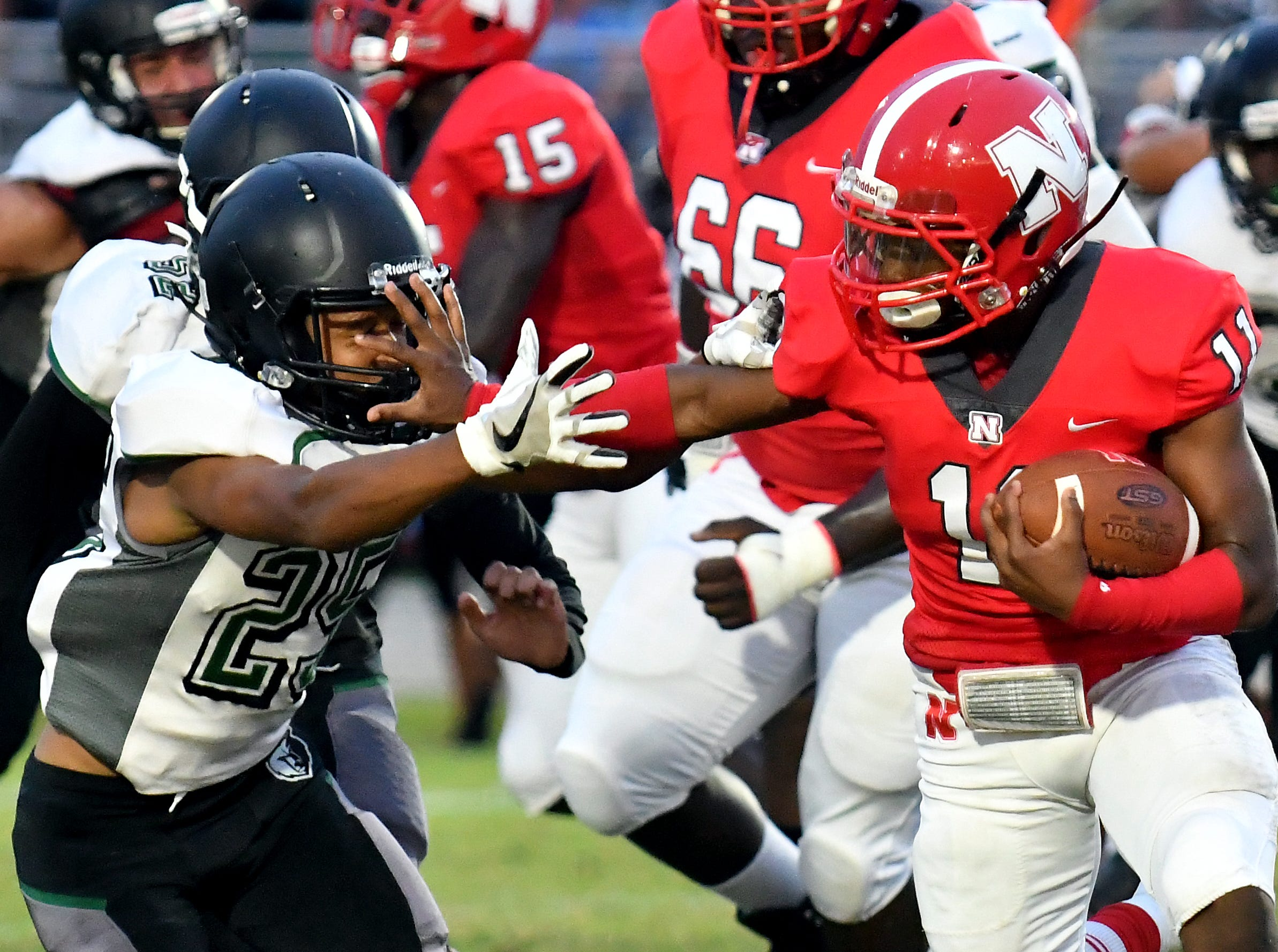 North Fort Myers High School running back Shomari Manson (11) stiff arms defender Julian Valentin (25) during their game with Palmetto Ridge High School, Friday, Sept. 7, 2018. (Chris Tilley/Special to the Naples Daily News)