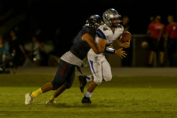 Estero's Marcos De la Cruz almost strips the ball loose from Bulldog quarterback Evan Hubbard as he tackles him from behind.