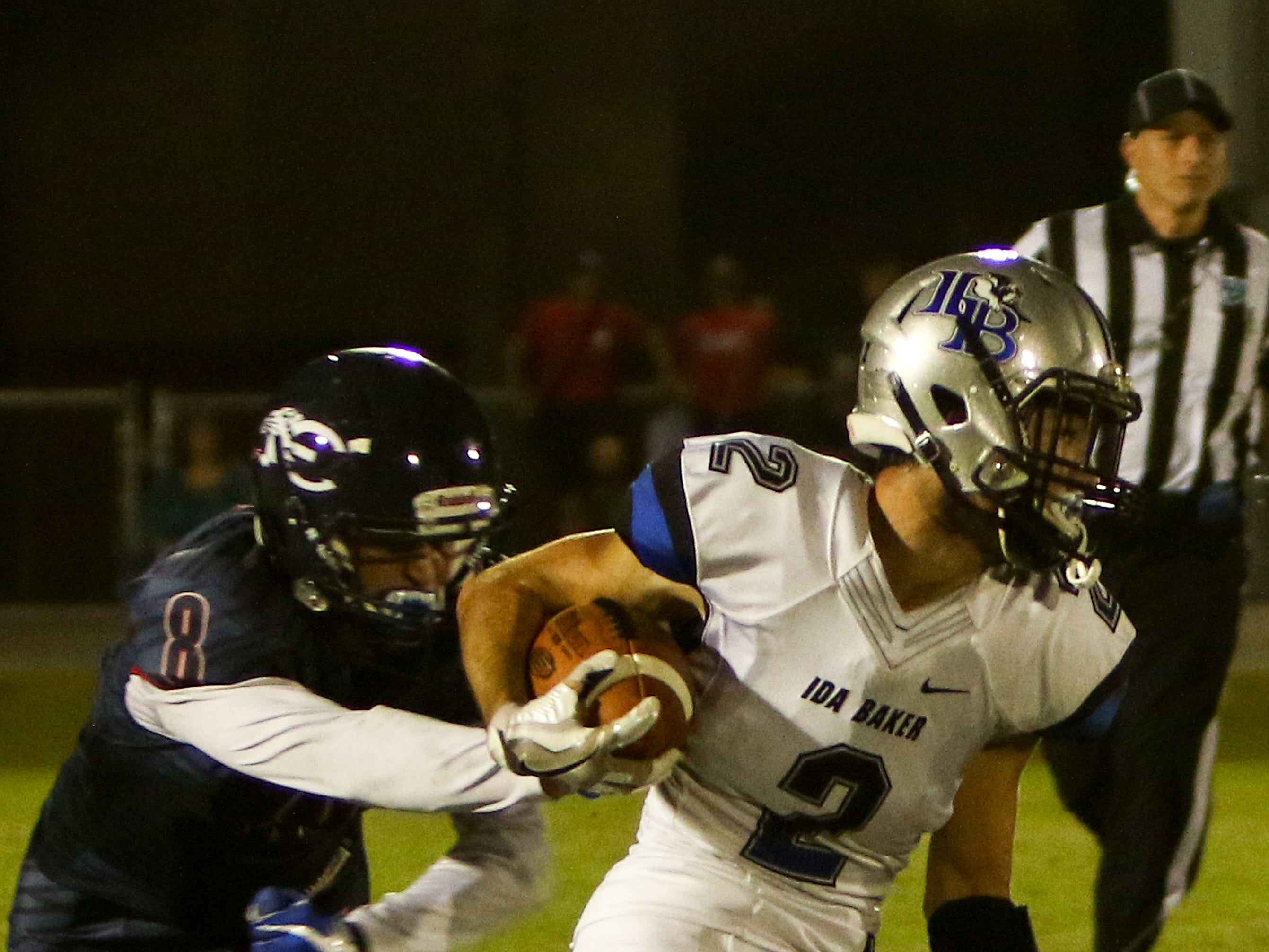 Estero's Bryce Ortengren tries to strip the ball from Bulldog receiver Patrick Mccabe.