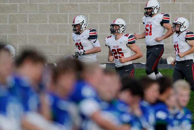 Pulaski players take the field to face Green Bay Notre Dame on Friday.
