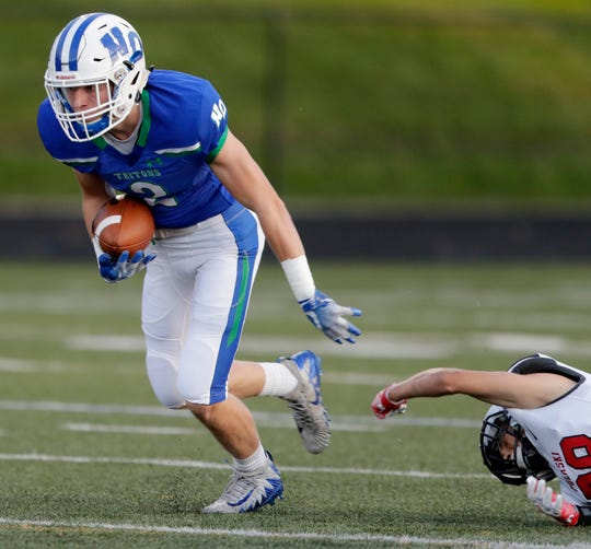 Notre Dame's Tommy Martzahl (2) breaks a tackle after a catch against Pulaski in a high school football game at Notre Dame Academy on Friday, September 7, 2018 in Green Bay, Wis.