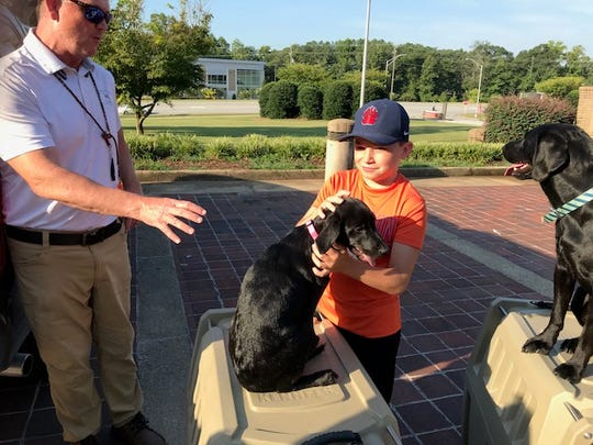 Parrish Major gives pup Halley to a surprised Sam Morrison at Shriners Hospital for Children Greenville.