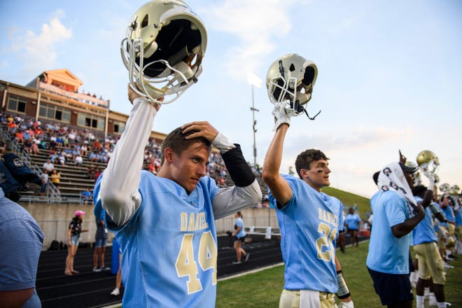 Daniel's Troy Johnson (44) and Daniel's Alex Joplin (21) raise their helmets during kickoff in the first quarter of their game against Westside on Friday, Sept. 7, 2018.