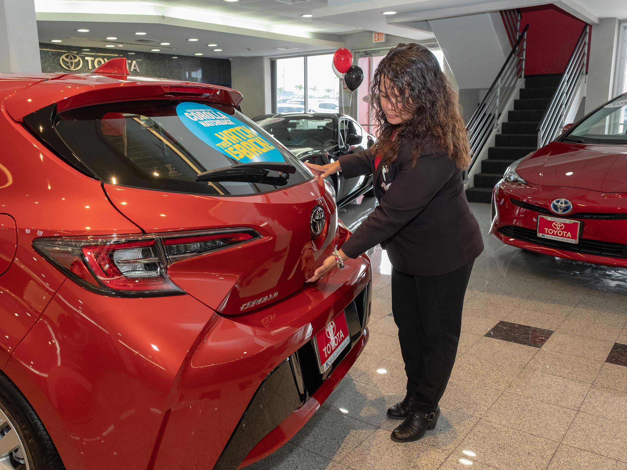 Mona Cing, a sales associate for Atkins Kroll Toyota opens the rear hatch of the 2019 Toyota Corolla in the showroom Sept. 8, 2018.