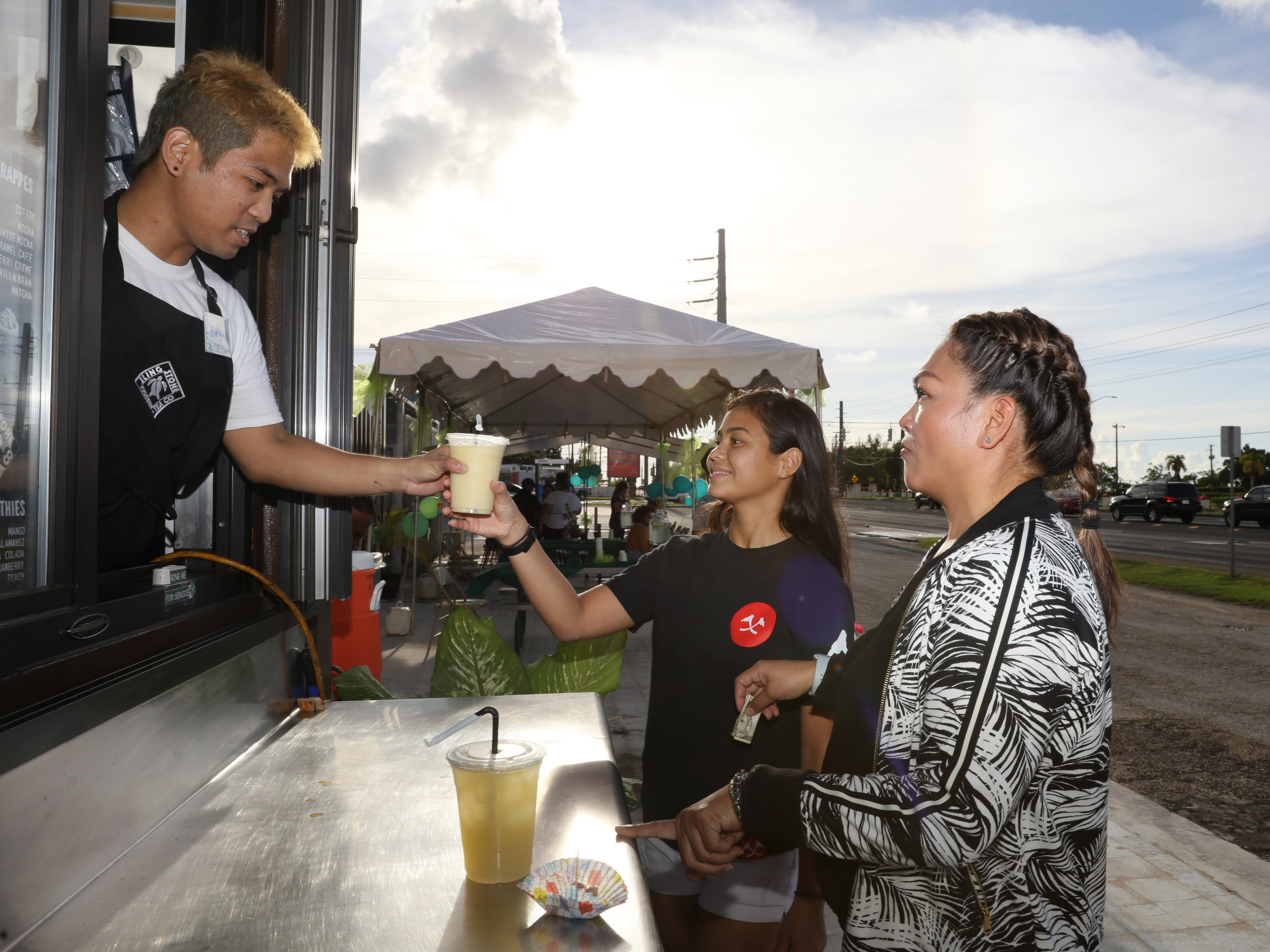 Sylvia Perez, center, receives her order at the Sling Stone Coffee during its grand opening in Anigua.