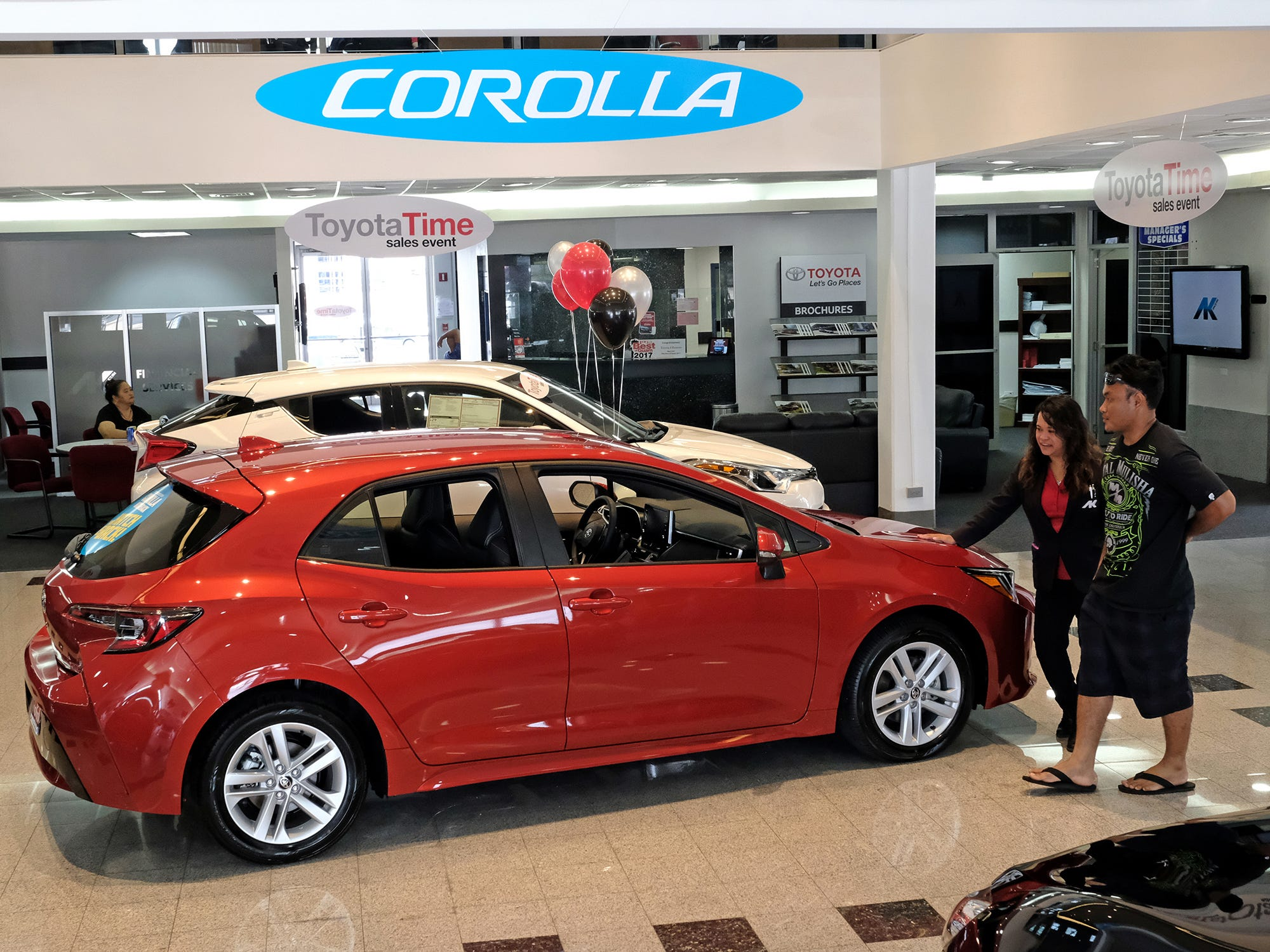 Atkins Kroll Toyota sales associate Mona Cing shows the 2019 Toyota Corolla hatchback to Andrew Milfith of Tamuning in the showroom Sept. 8, 2018.