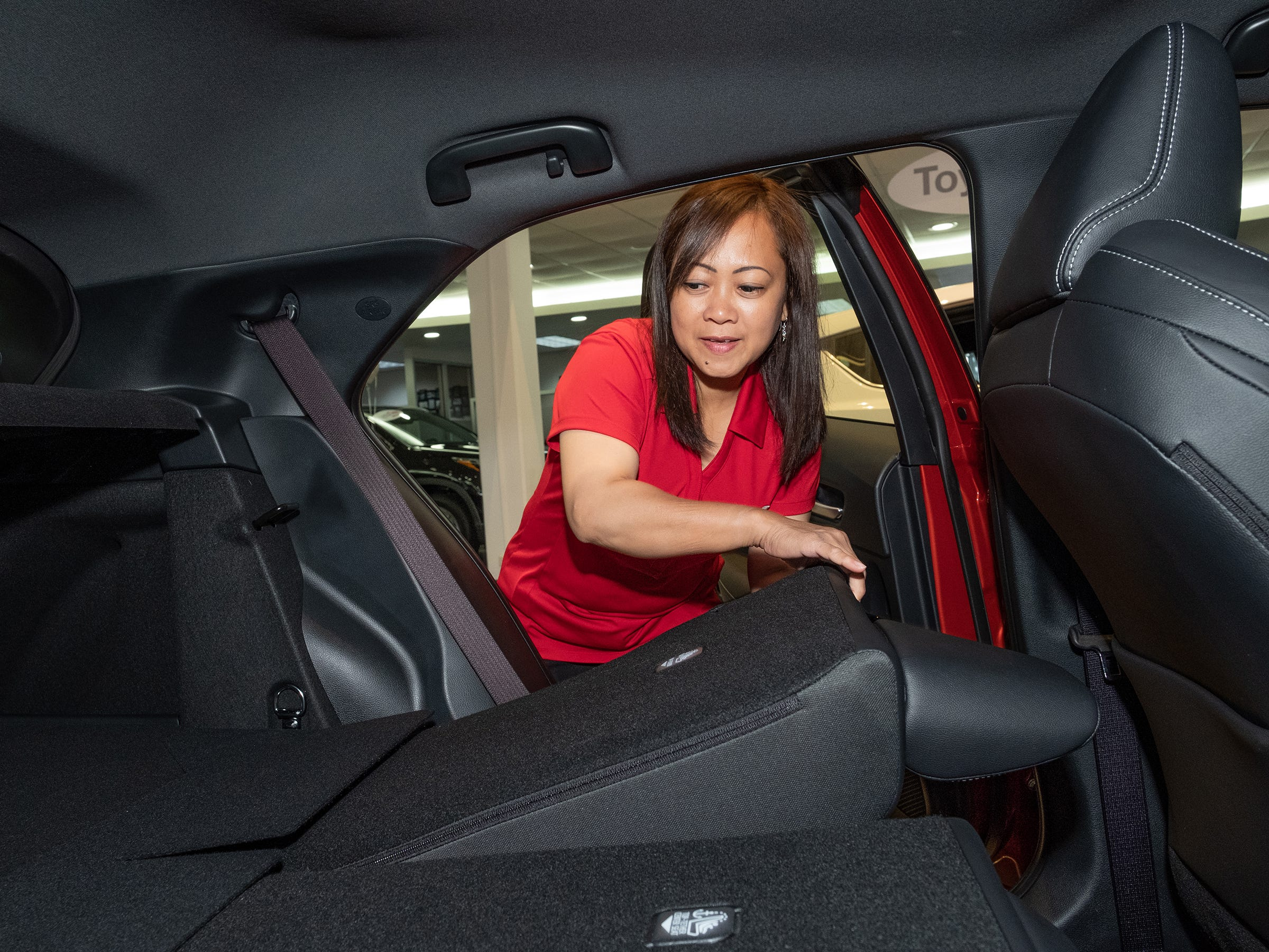 Cathy Ignacio, a sales associates for Atkins Kroll Toyota, lowers the seat of the 2019 Toyota Corolla hatchback in the showroom Sept. 8, 2018.