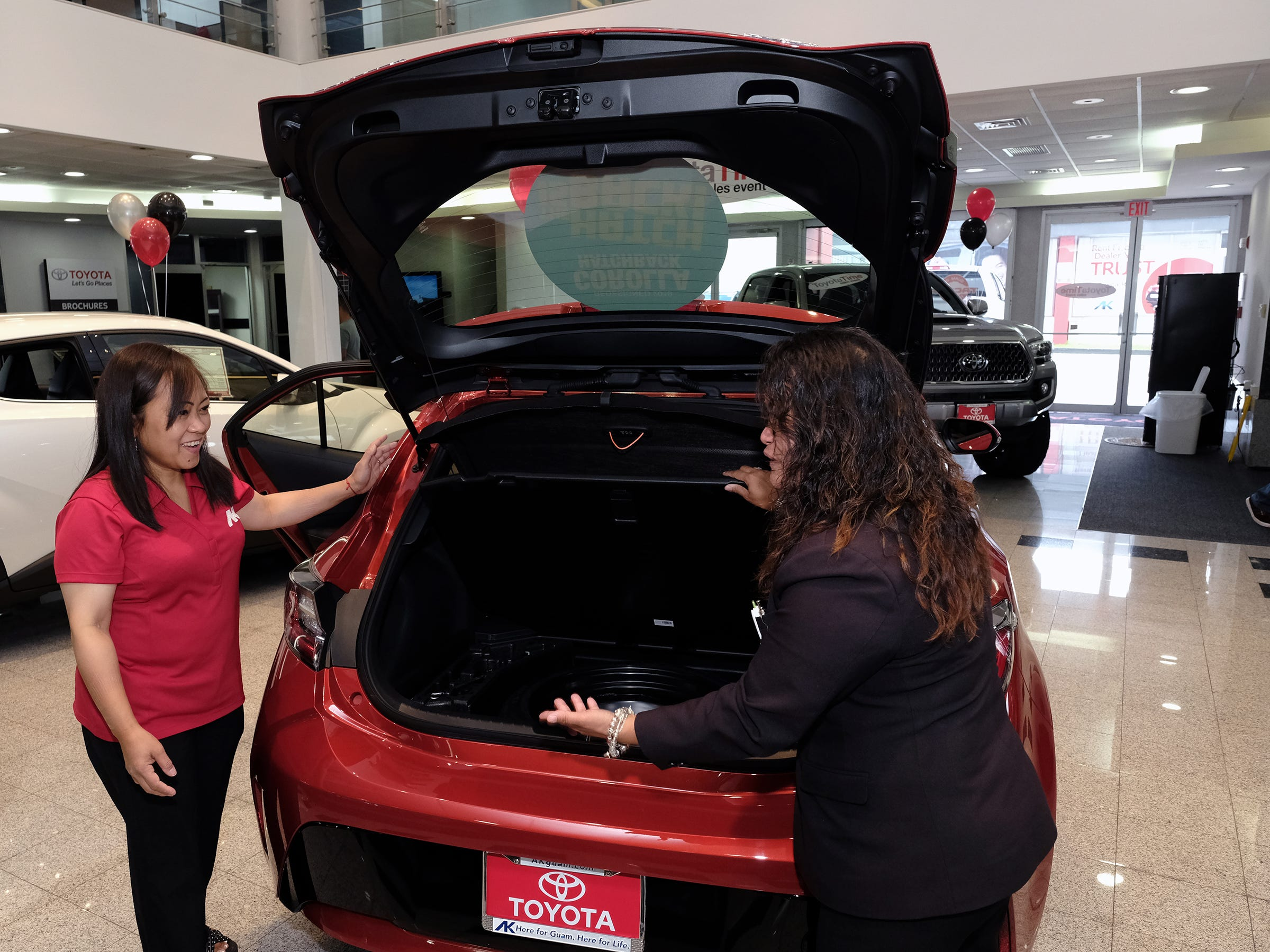 Cathy Ignacio, left, and Mona Cing, sales associates for Atkins Kroll Toyota, open the hatchback of the 2019 Toyota Corolla in the showroom Sept. 8, 2018.