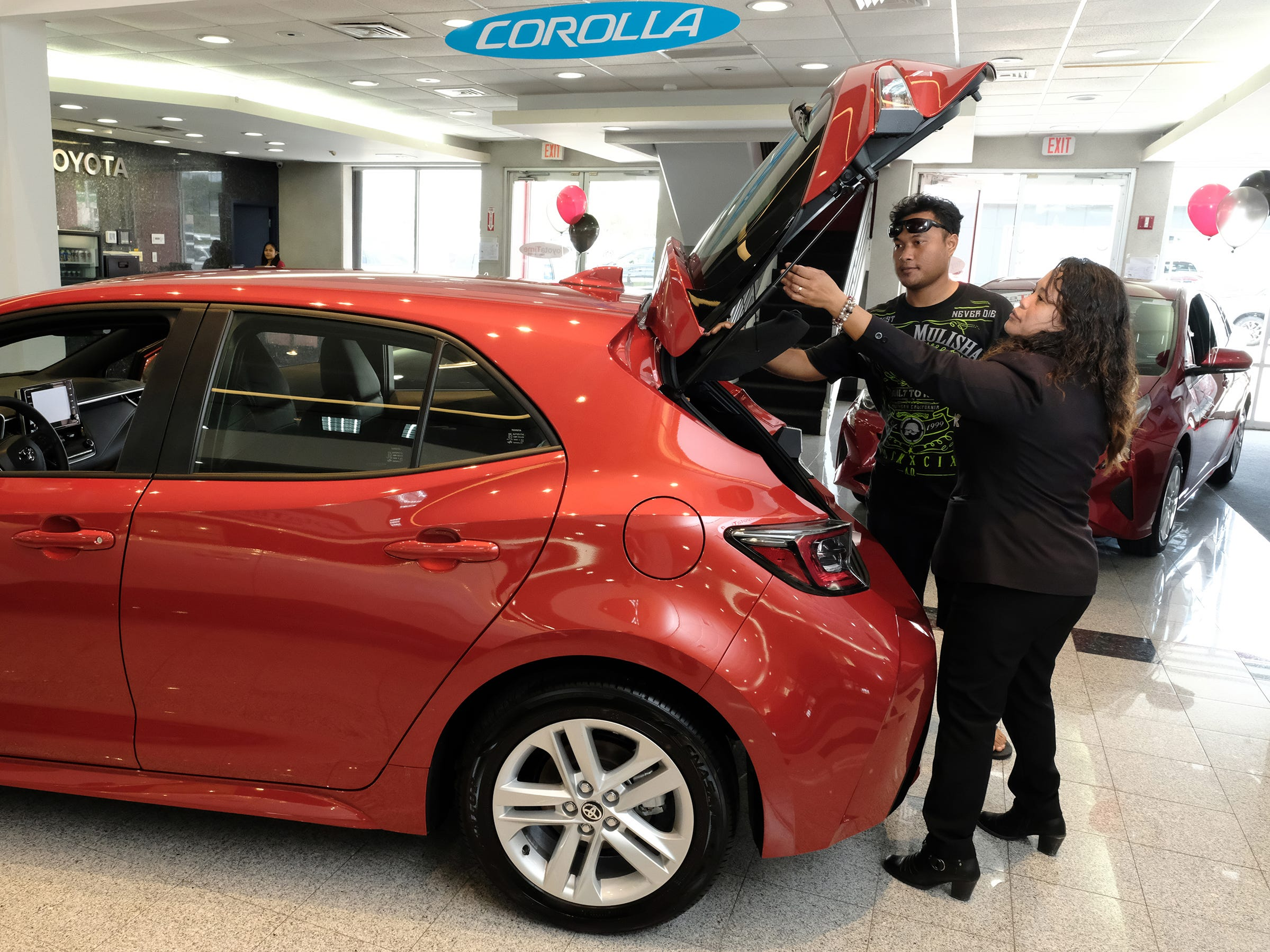 Atkins Kroll Toyota sale associate Mona Cing shows the 2019 Toyota Corolla hatchback to Andrew Milfith of Tamuning in the showroom Sept. 8, 2018.