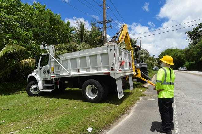 Guam Power Authority employees work to clear vegetation from power lines in preparation for Tropical Storm Mangkhut in Agat on Sept. 8, 2018.