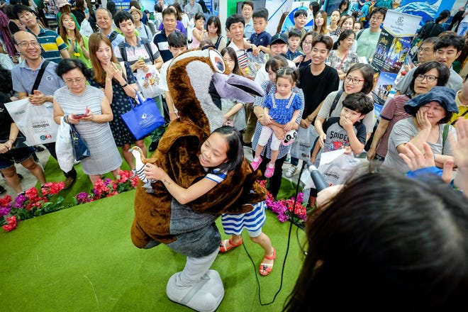 A young girl hugs Che'lu' the Ko'ko' bird at the Guam Pavilion at the 2018 Modetour Travel Mart in Seoul.
